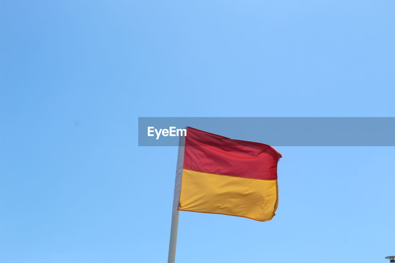 blue, flag, sky, low angle view, copy space, red, yellow, patriotism, nature, day, environment, wind, clear sky, no people, striped, waving, pride, pole