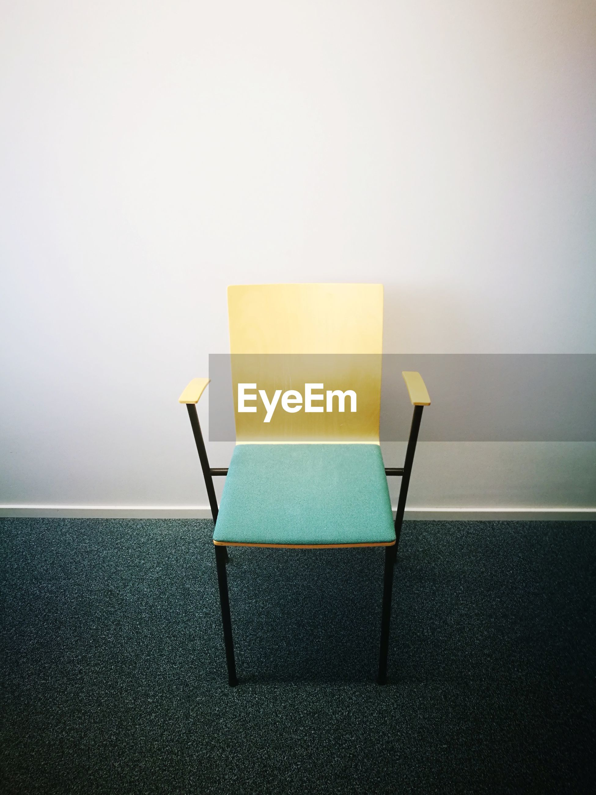 Close-up of empty chair against white wall