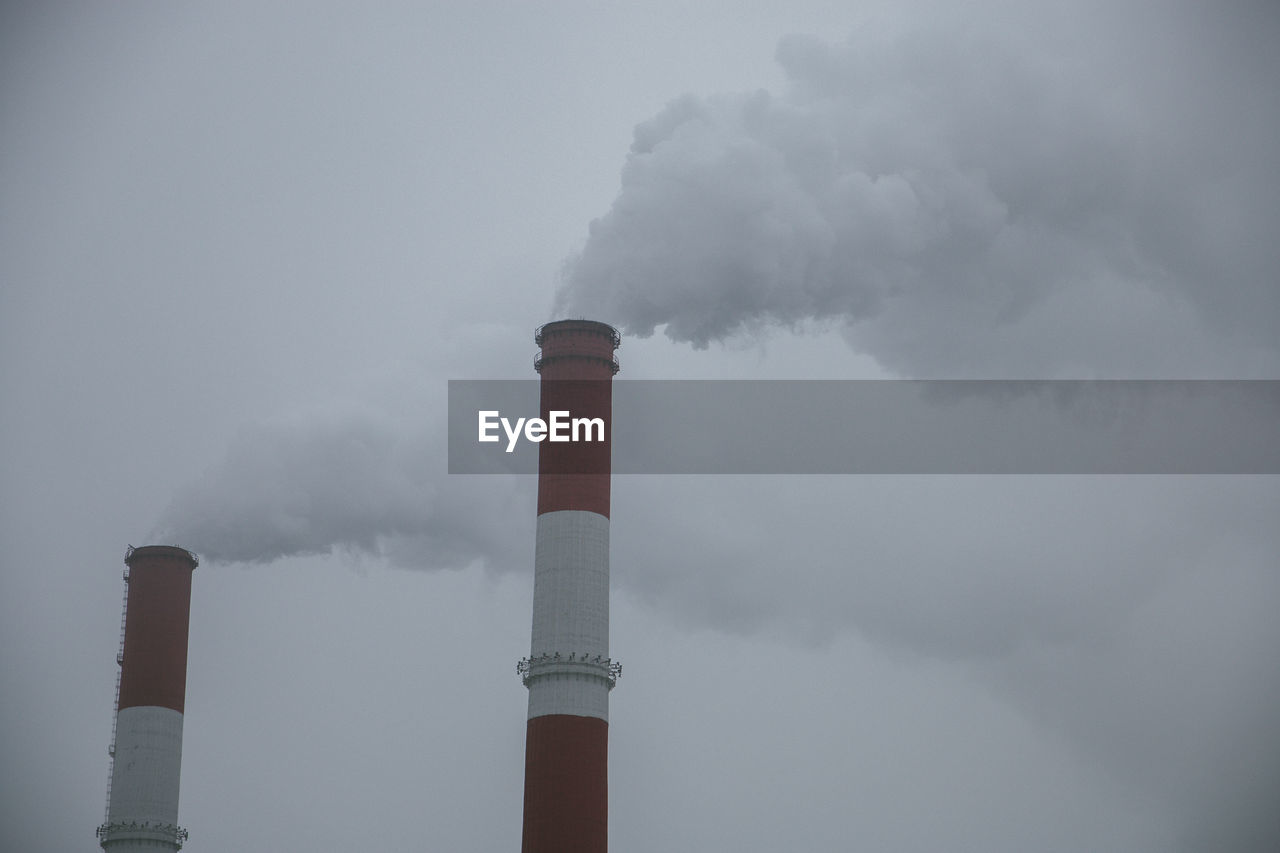 building exterior, pollution, factory, smoke stack, sky, environmental issues, industry, environment, cloud - sky, emitting, air pollution, built structure, smoke - physical structure, environmental damage, architecture, no people, chimney, low angle view, day, nature, tall - high, outdoors, fumes, ecosystem, atmospheric