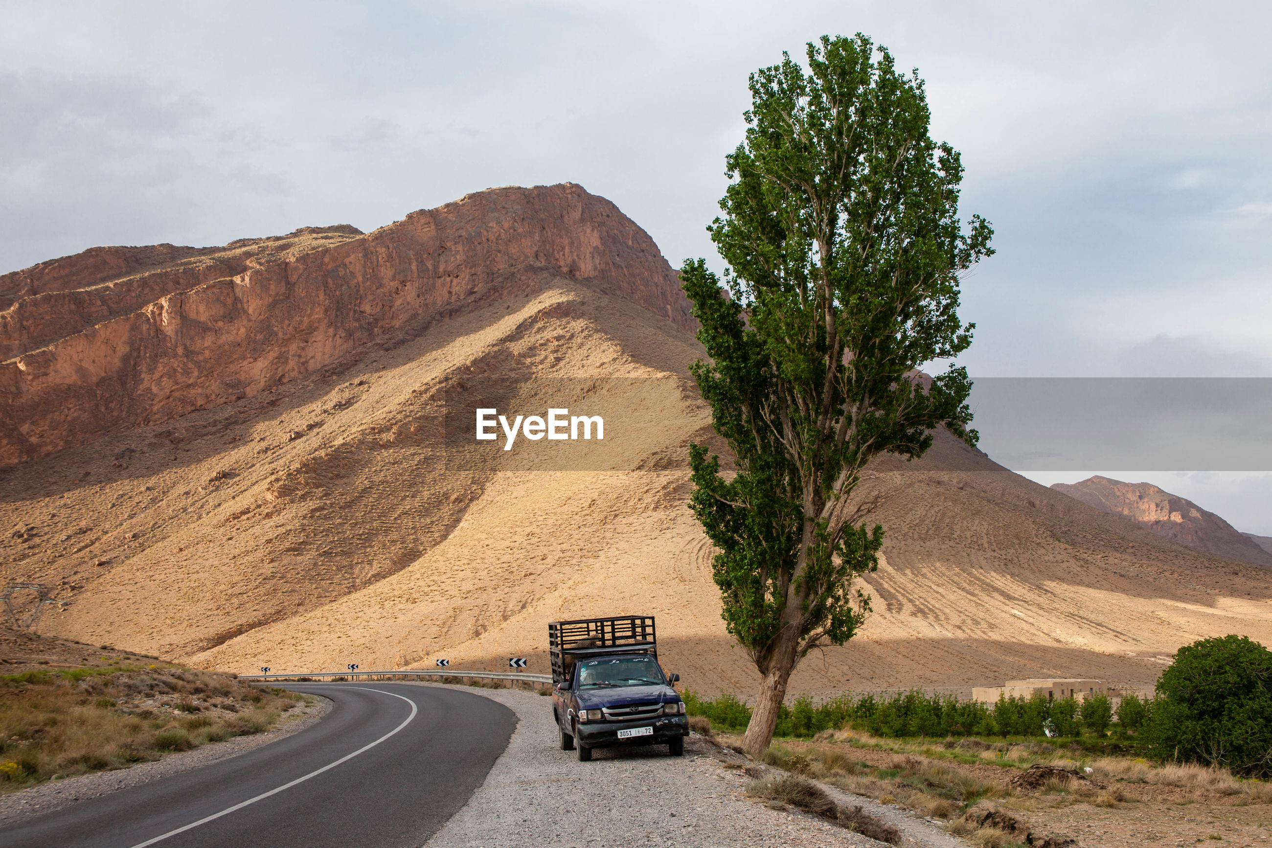 VEHICLES ON ROAD BY MOUNTAINS AGAINST SKY