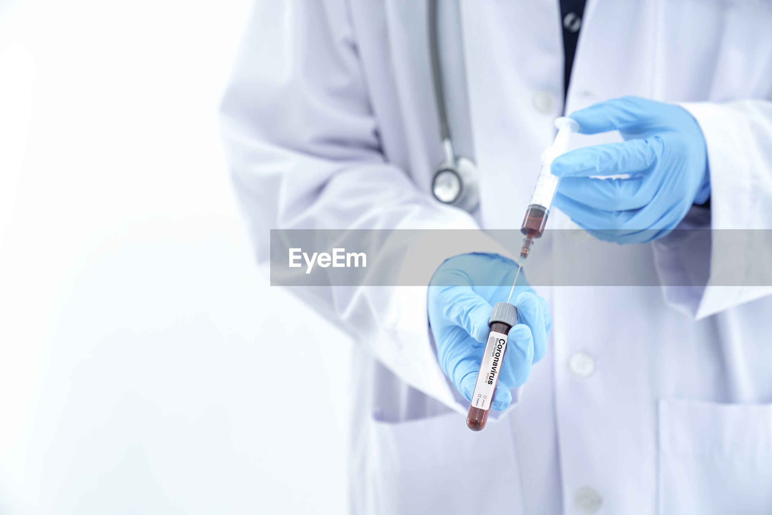 Midsection of doctor holding syringe against white background