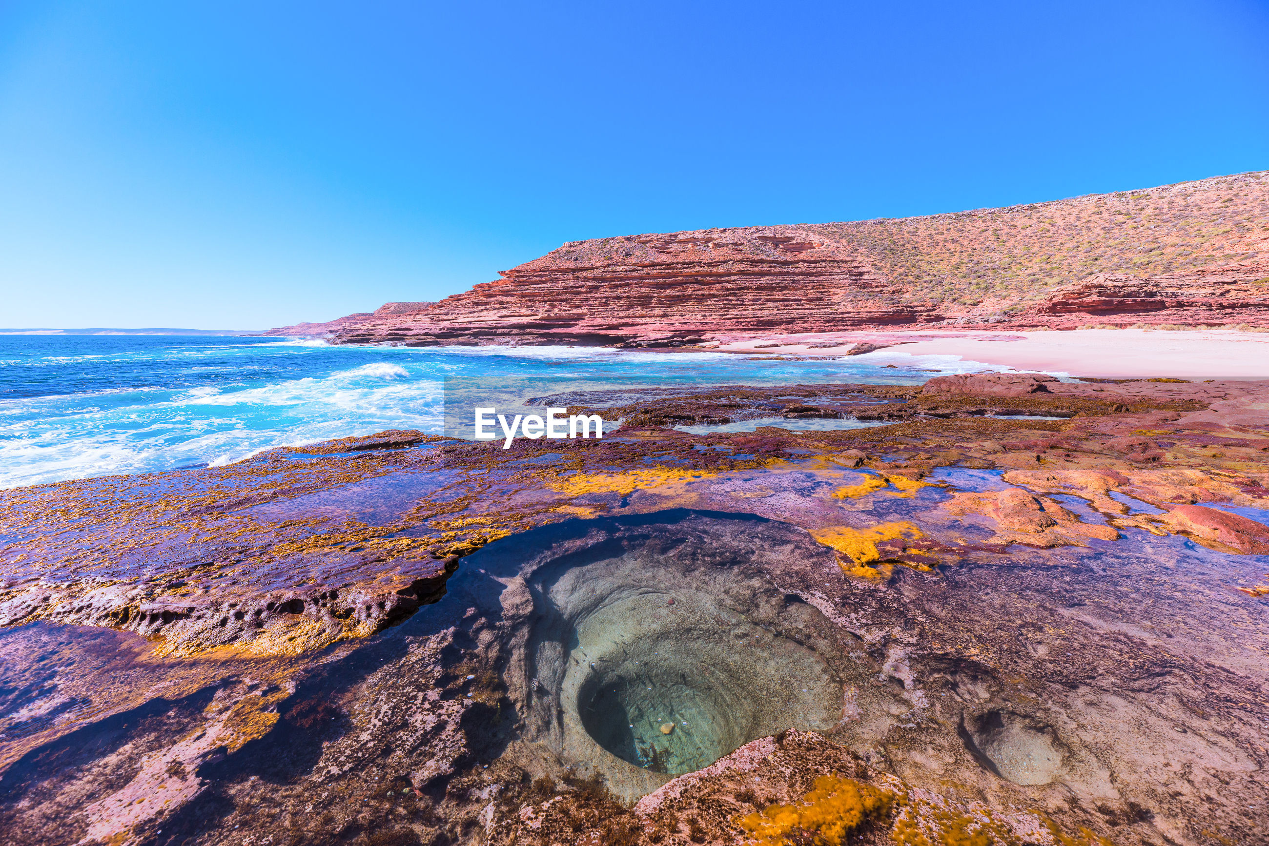Scenic view of rock formation at sea against clear blue sky