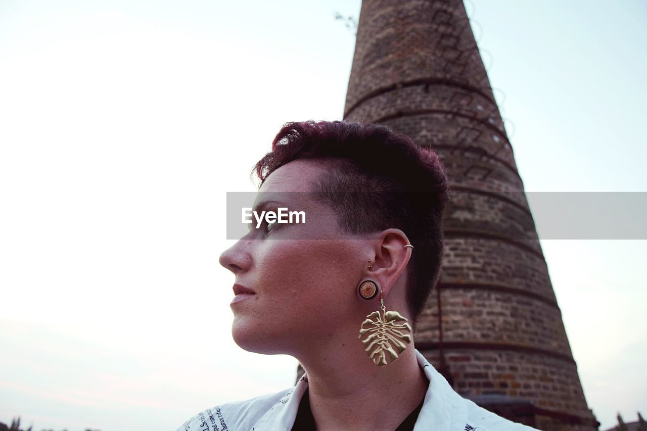 Young woman wearing earring while looking away against built structure