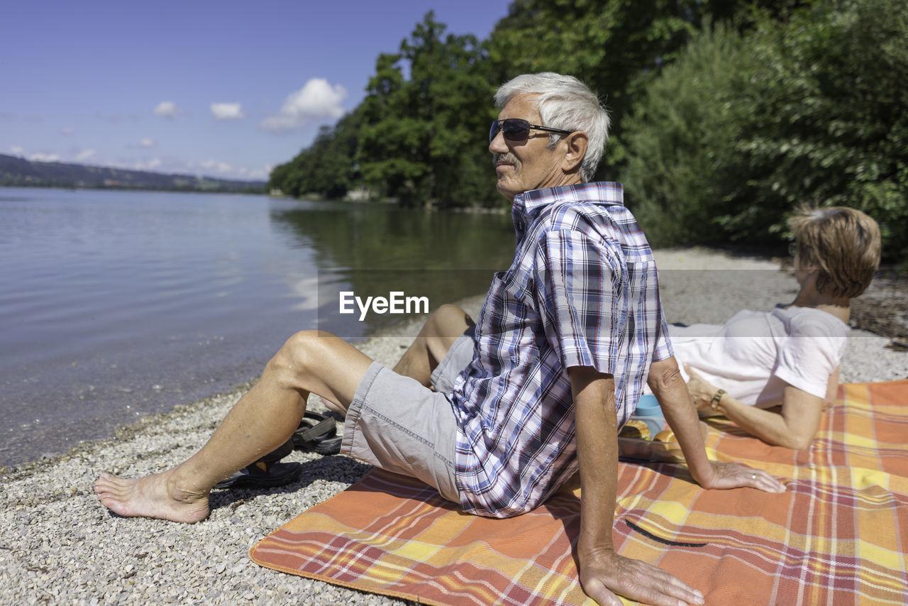 Senior Couple Sitting At Kochelsee Lakeshore
