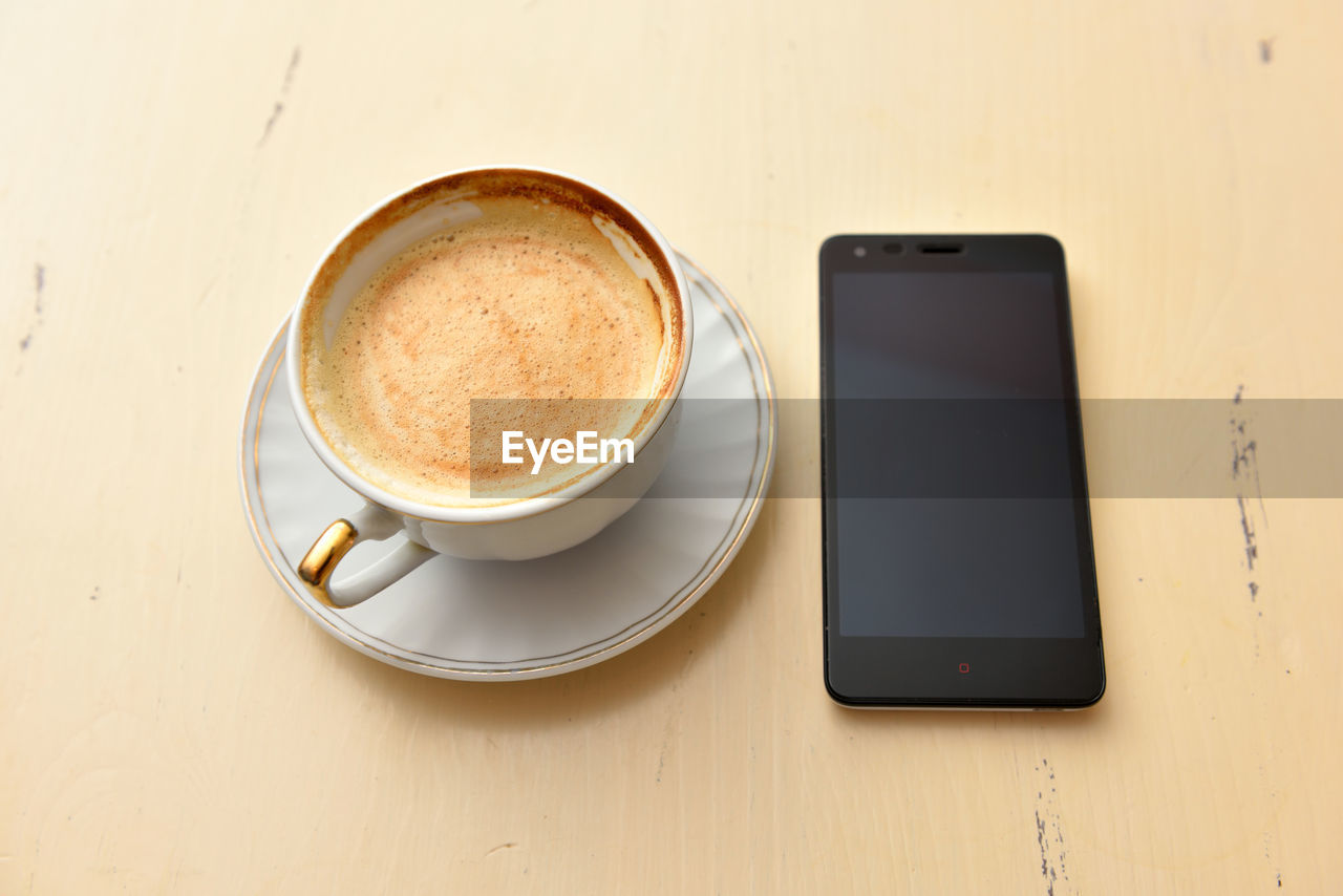 food and drink, drink, refreshment, table, wireless technology, technology, coffee, portable information device, coffee - drink, smart phone, cup, still life, mug, crockery, mobile phone, coffee cup, saucer, communication, connection, freshness, no people, hot drink, frothy drink