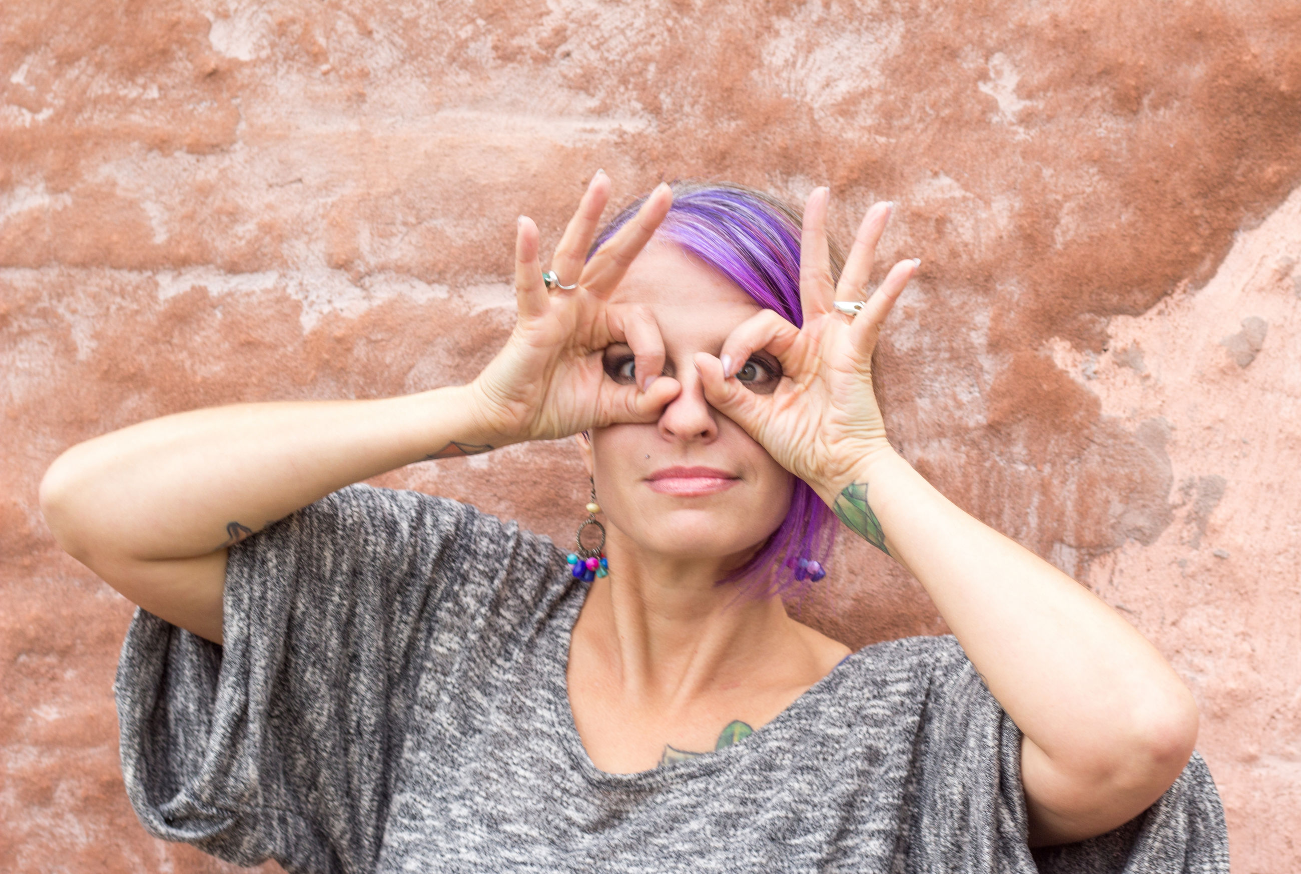 Portrait of woman making mask with hands against wall