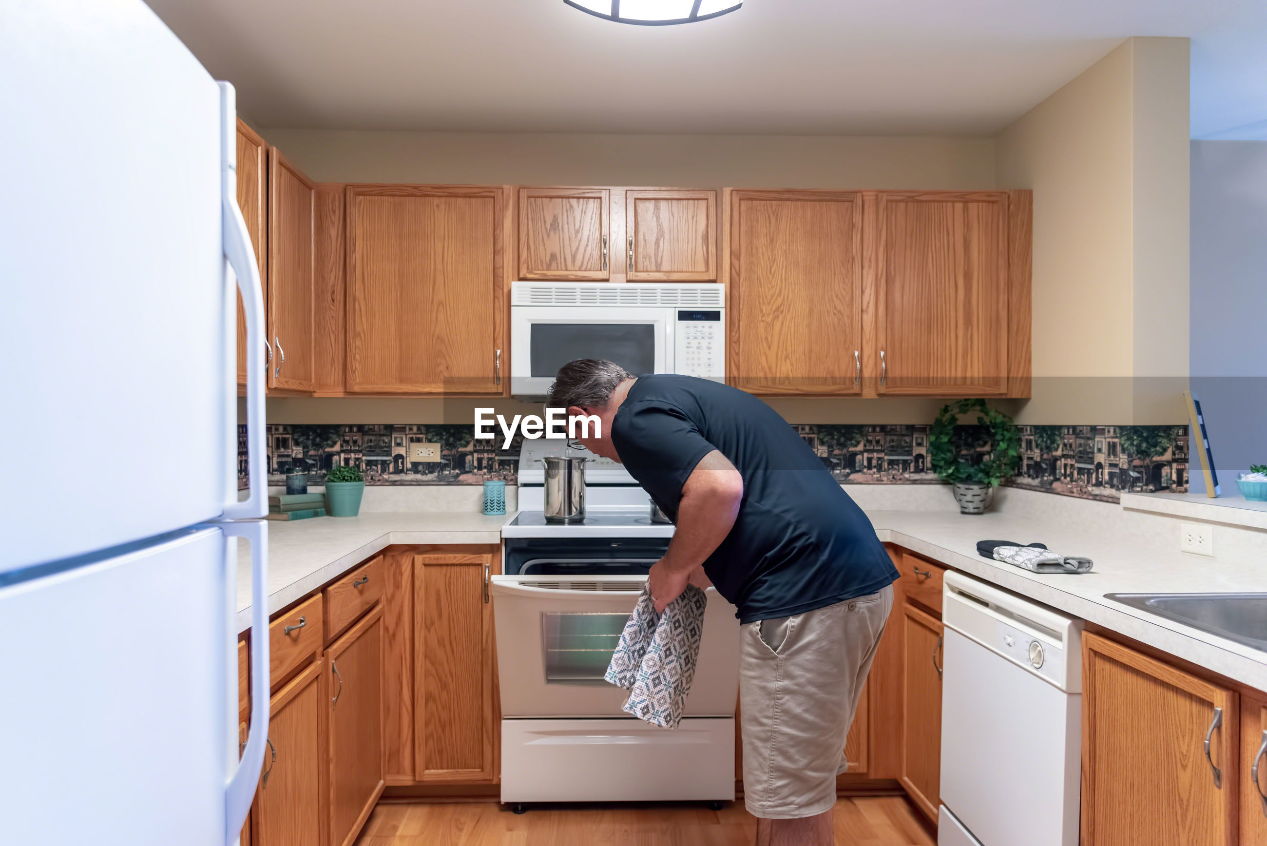 Man opening oven in kitchen at home
