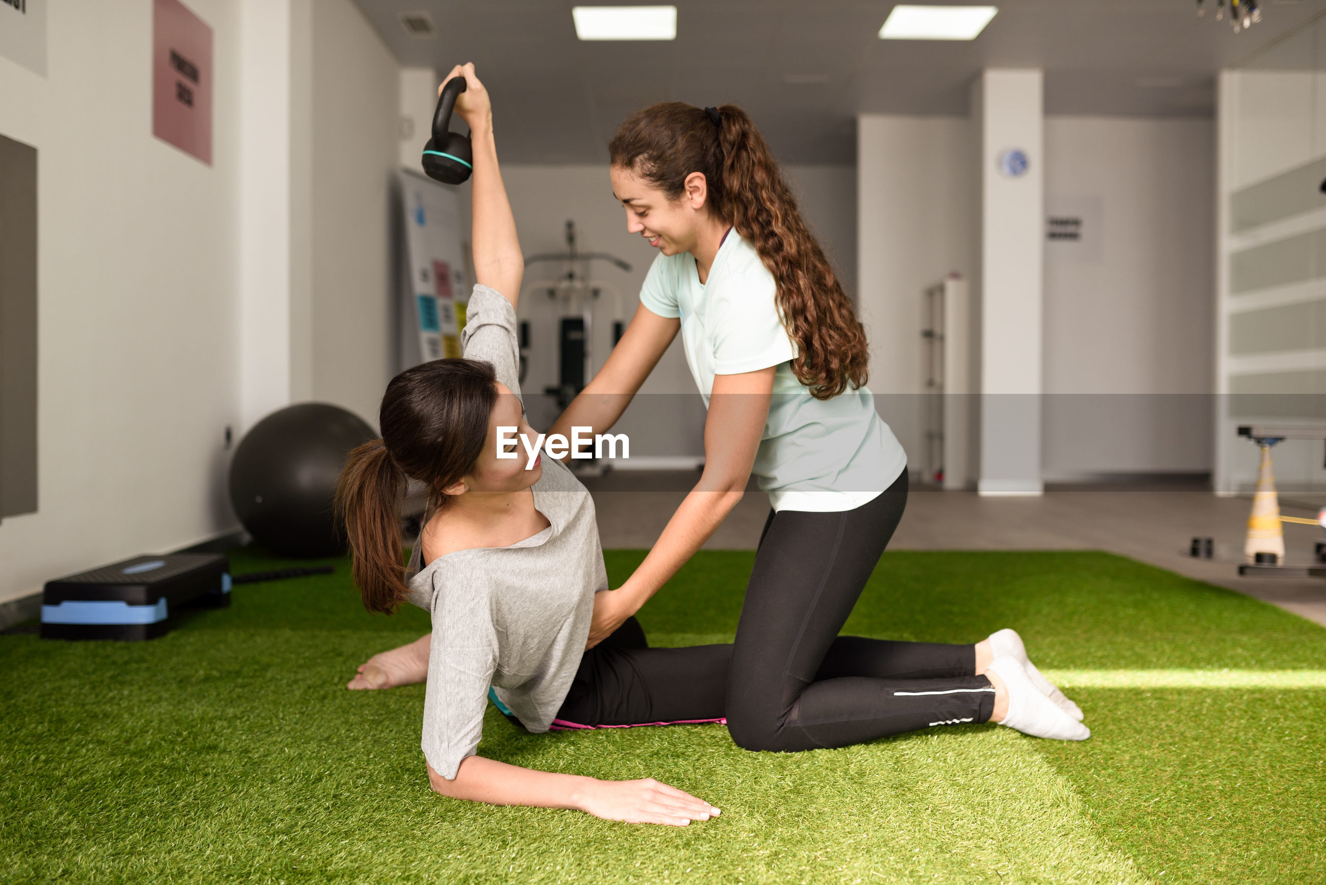 Instructor assisting woman exercising at gym