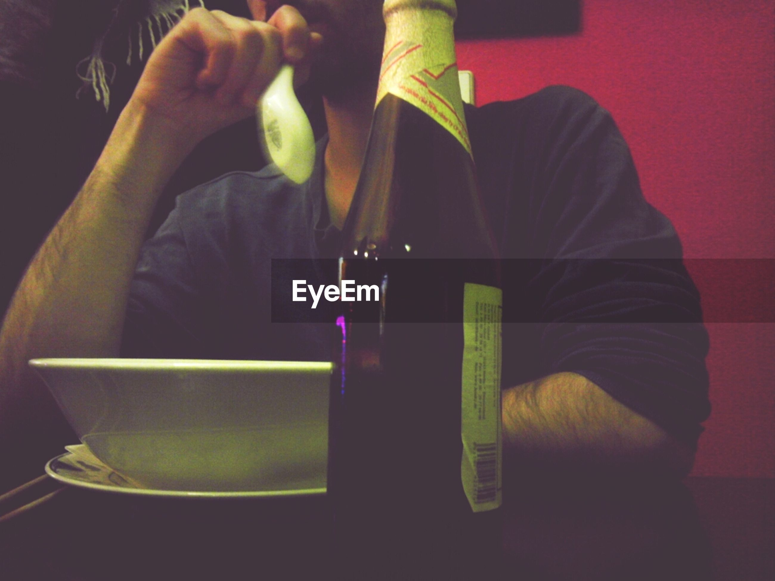 Low angle view of beer bottle in front of man sitting in restaurant