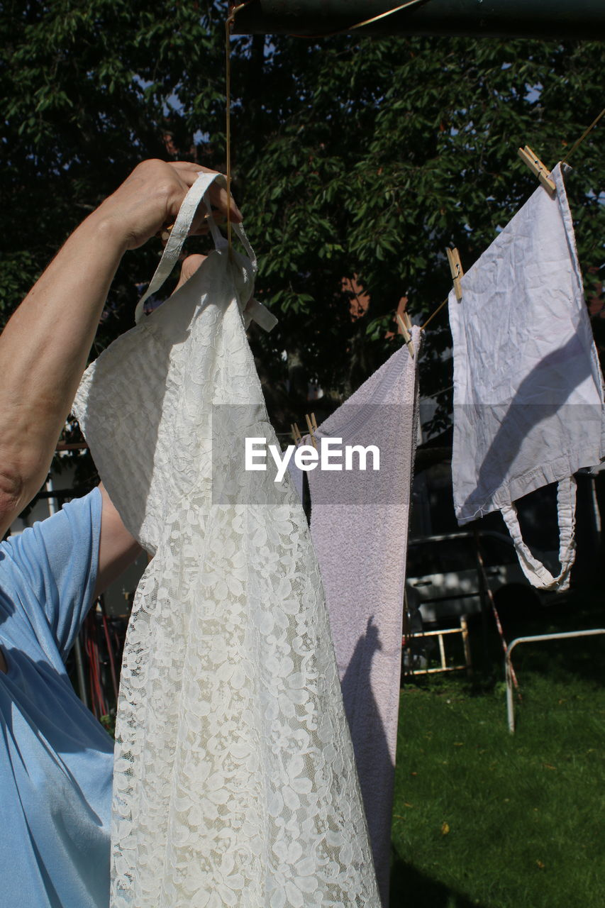 Side view of woman arranging wedding dress on clothesline