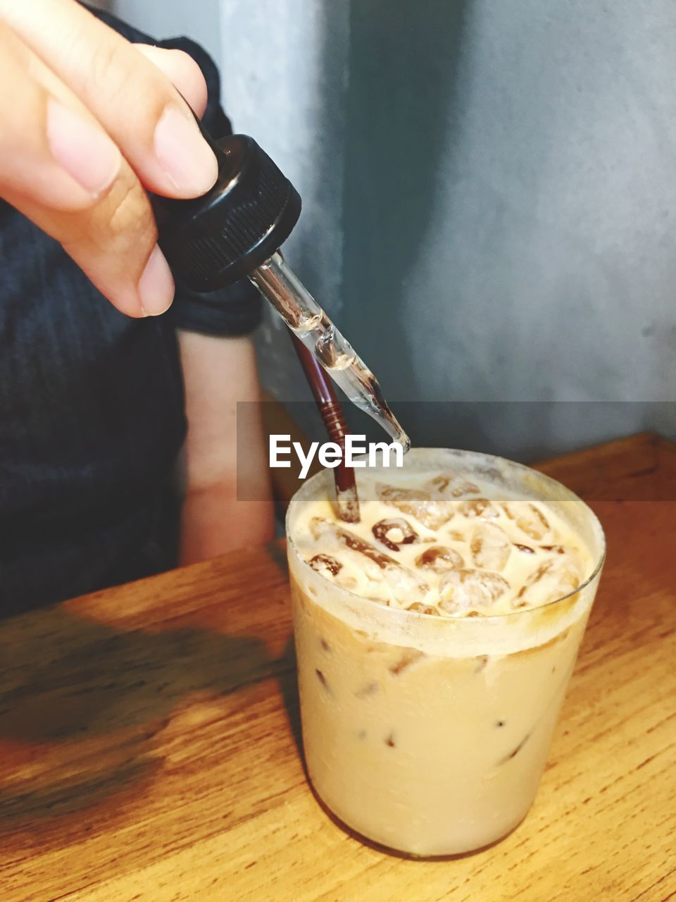 Cropped Image Of Person Adding Liquid In Iced Coffee Through Dropper At Restaurant