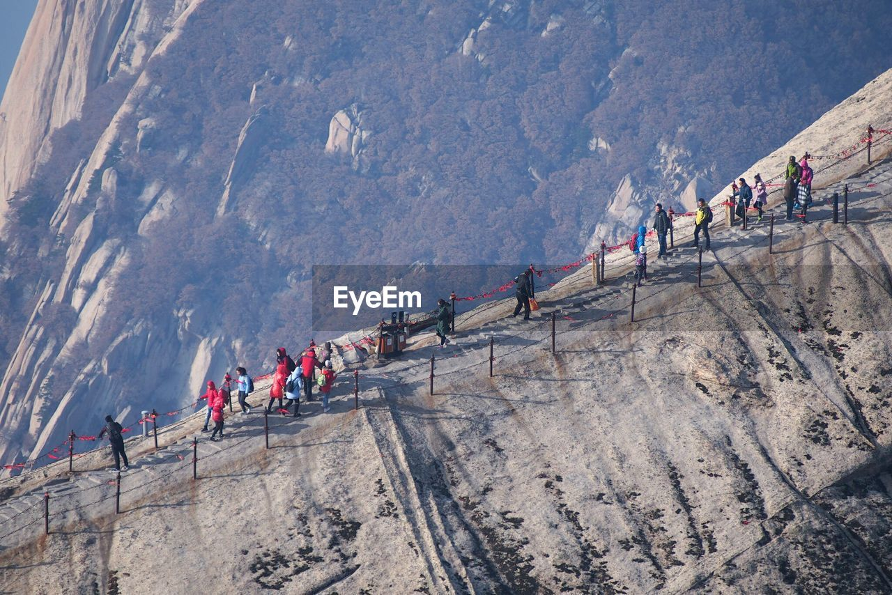 large group of people, mountain, men, real people, leisure activity, women, walking, mountain range, outdoors, day, nature, lifestyles, adventure, steep, physical geography, challenge, adult, sport, rock face, athlete, people, adults only, sportsman, young adult