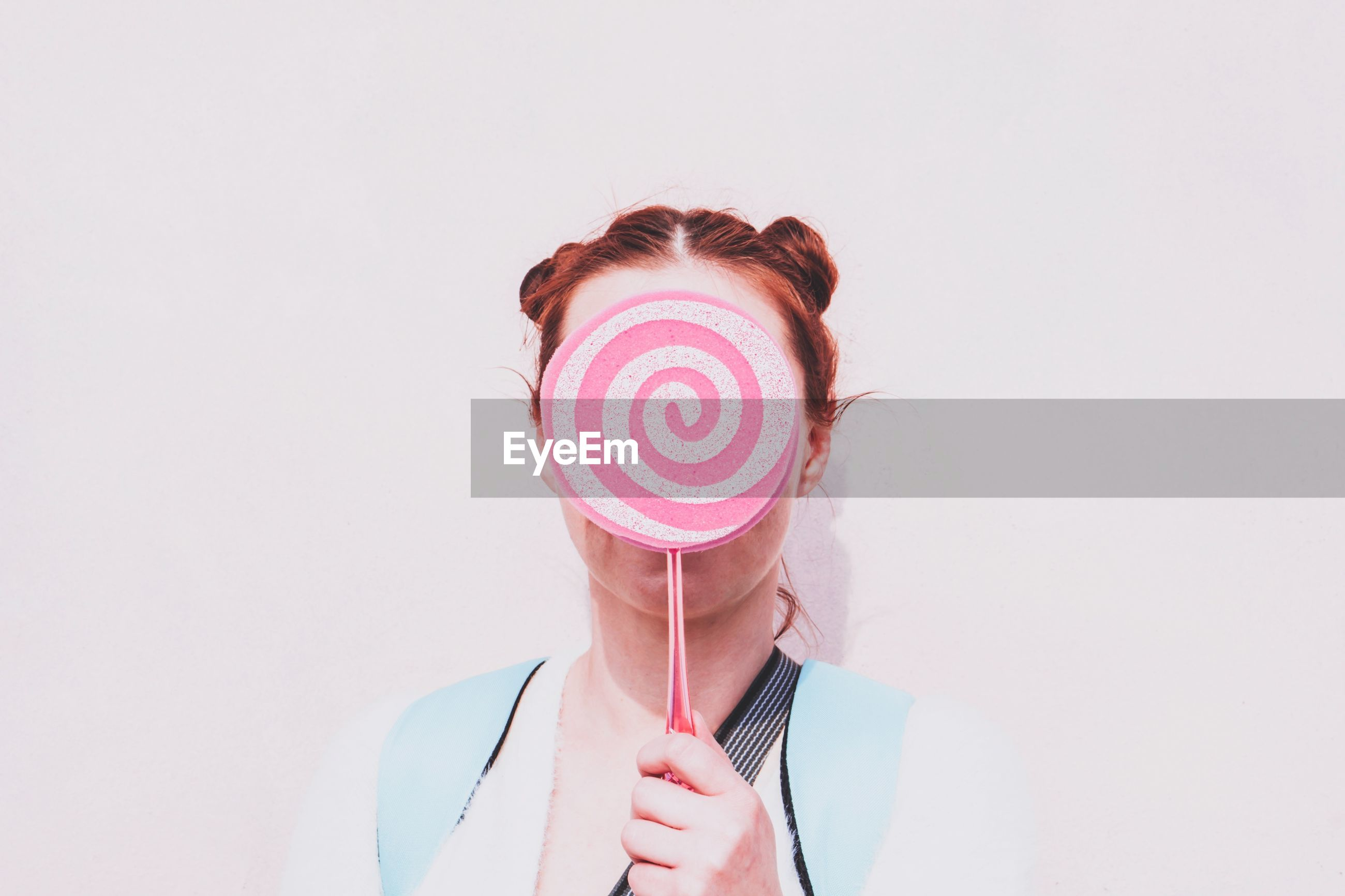 Close-up of woman holding candy against white background