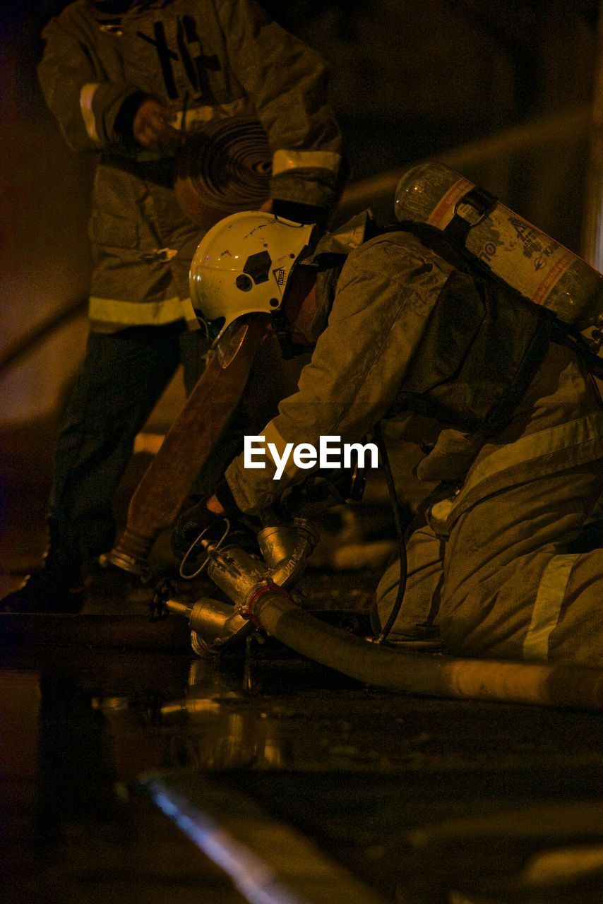 real people, selective focus, men, indoors, standing, one person, occupation, skill, welder, night, illuminated, working, protective workwear, one man only, metal industry, occupational safety and health, people