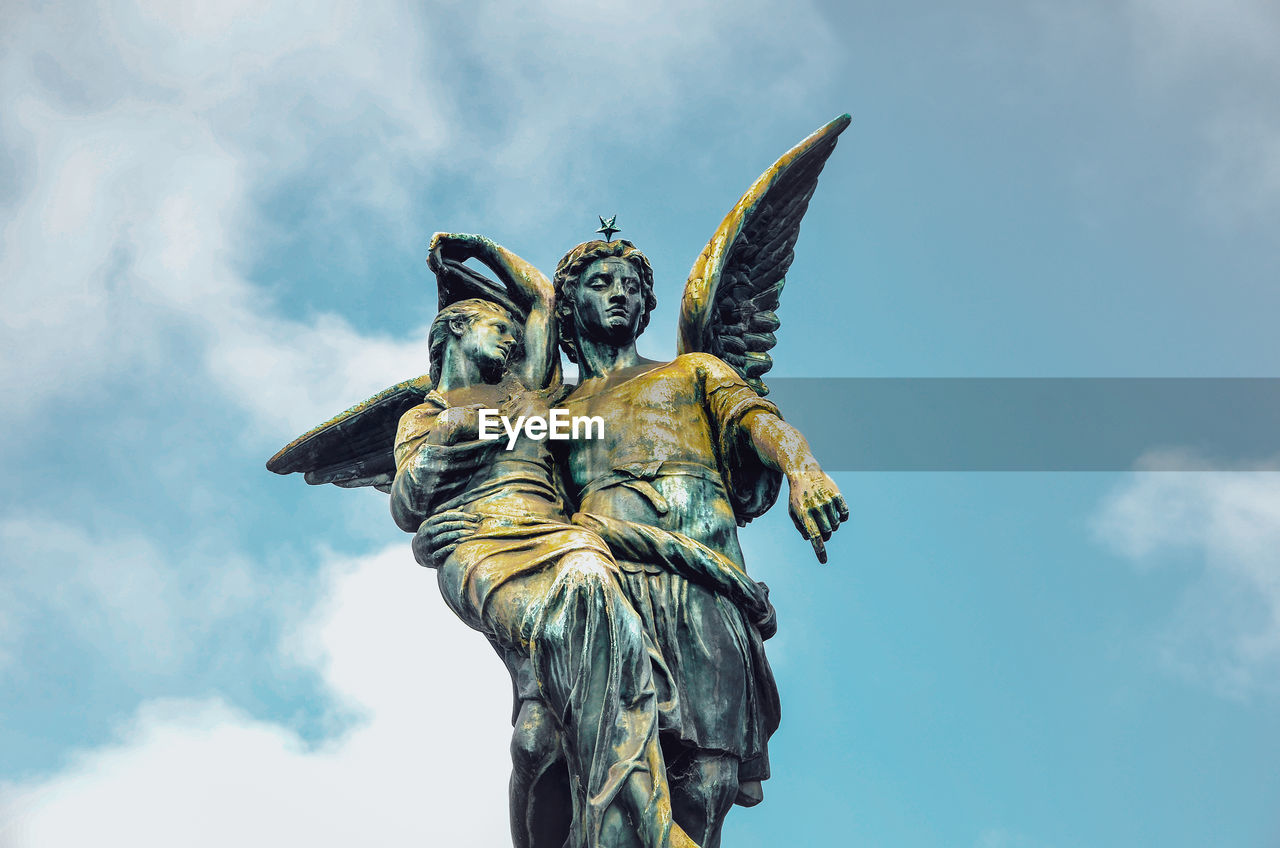 sculpture, human representation, representation, statue, art and craft, low angle view, sky, cloud - sky, creativity, no people, day, male likeness, nature, craft, religion, gold colored, female likeness, belief, outdoors, angel, angle, ornate