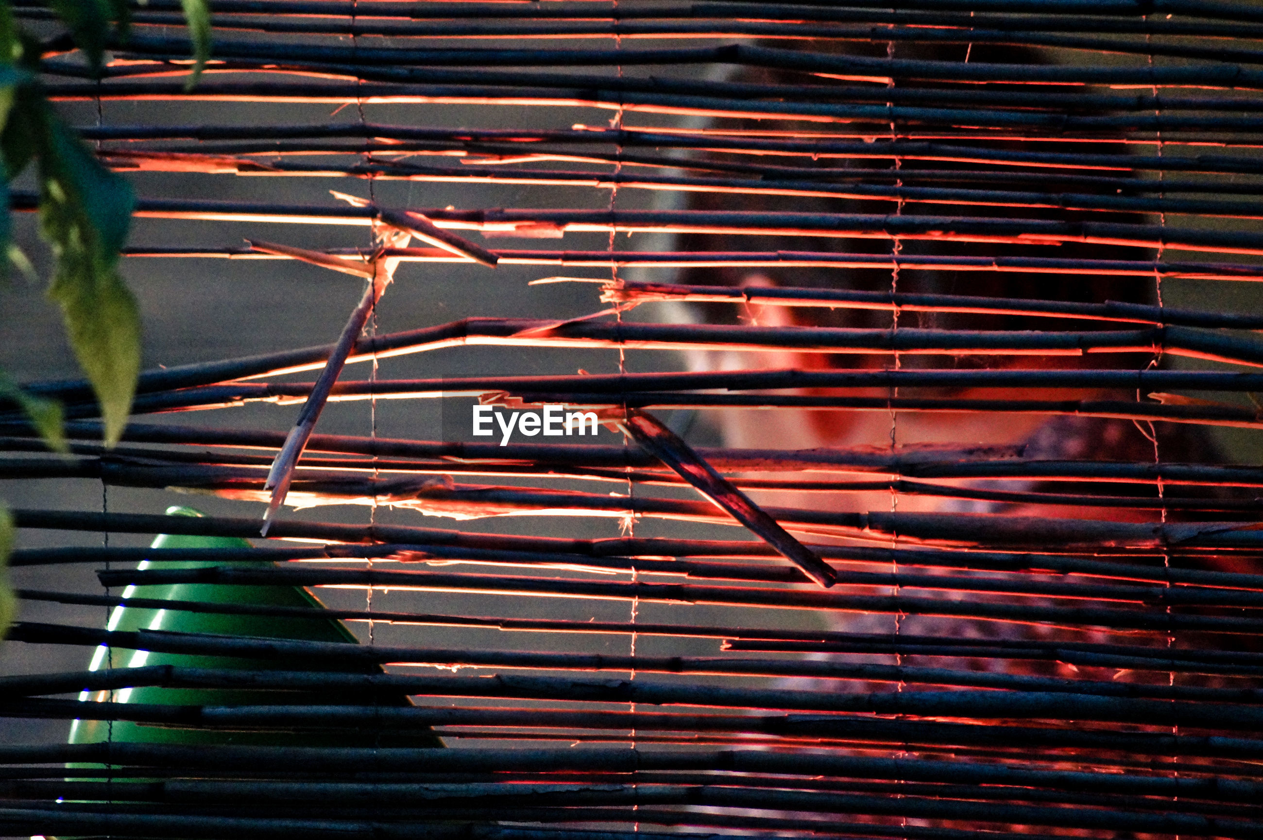 Low angle view of man seen through damaged bamboo curtain