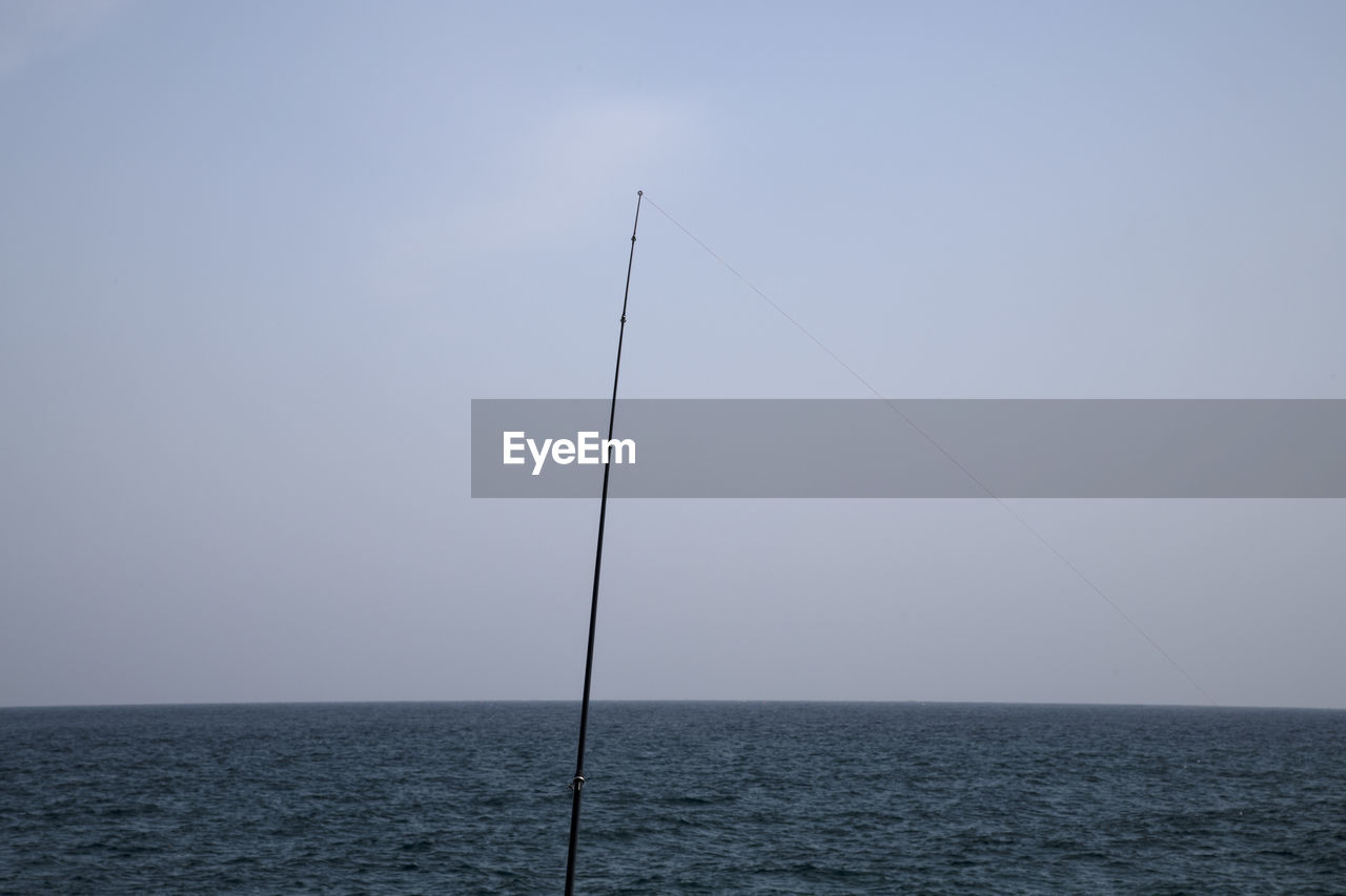 sea, water, sky, horizon over water, horizon, tranquil scene, scenics - nature, tranquility, beauty in nature, waterfront, no people, nature, day, clear sky, copy space, outdoors, remote, rod, fishing rod, sailboat