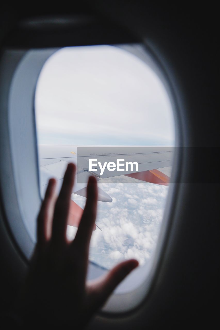 Cropped Hand On Airplane Window Against Aircraft Wing