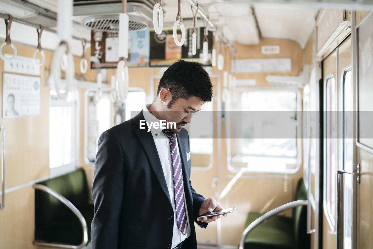 MAN STANDING BY TRAIN IN BUS