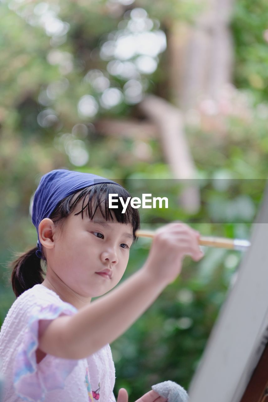 Cute asian child girl is holding paintbrush and painting on the paper. selective focus