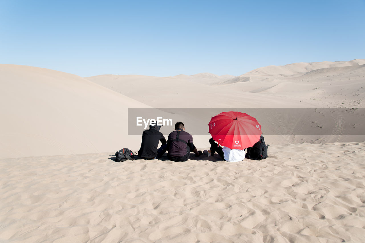 sand, desert, real people, sand dune, arid climate, men, togetherness, lifestyles, leisure activity, nature, day, clear sky, sitting, outdoors, full length, two people, women, landscape, beauty in nature, friendship, mammal, sky, people