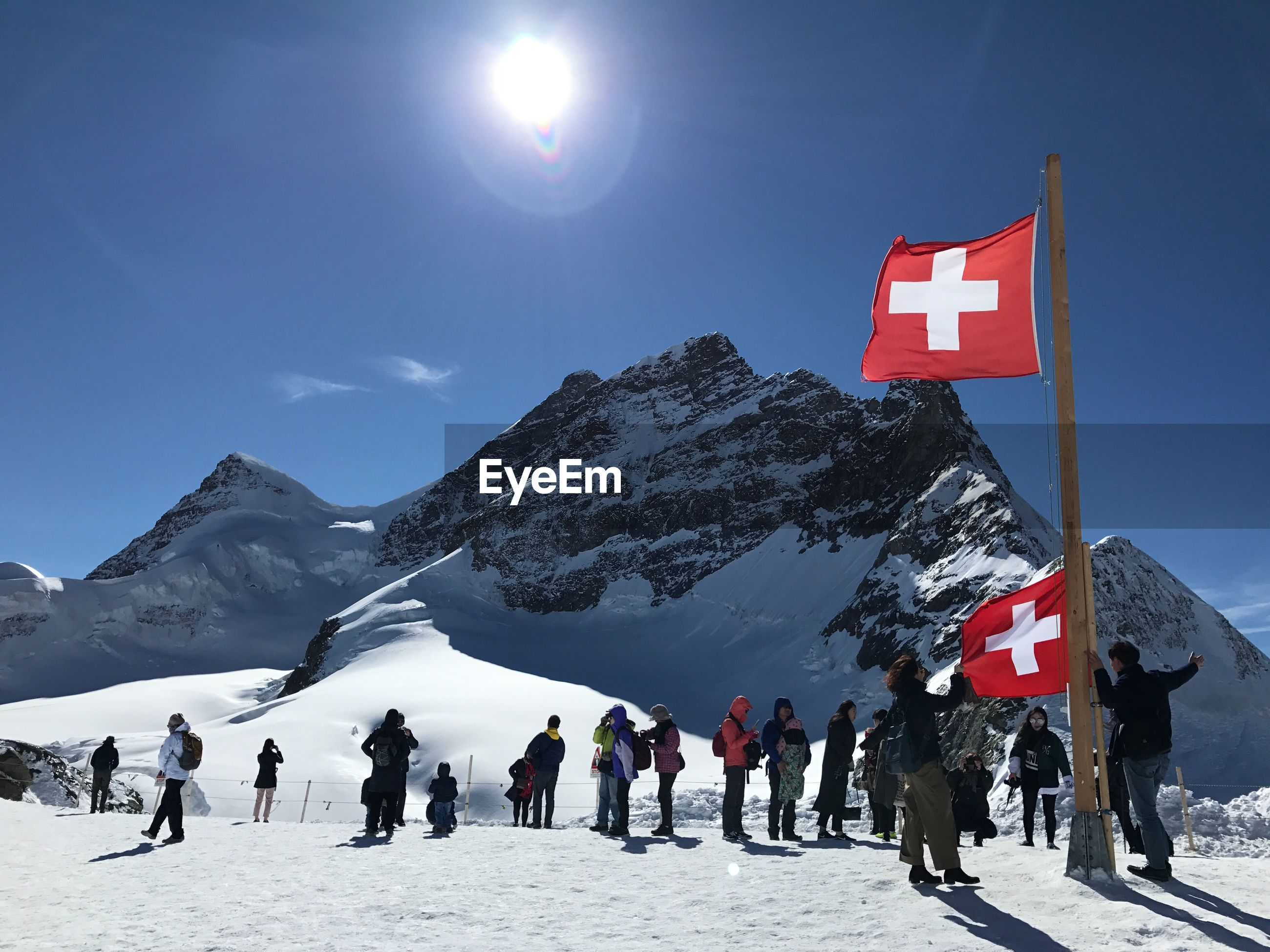 People and swiss flags on snowcapped mountain against clear blue sky