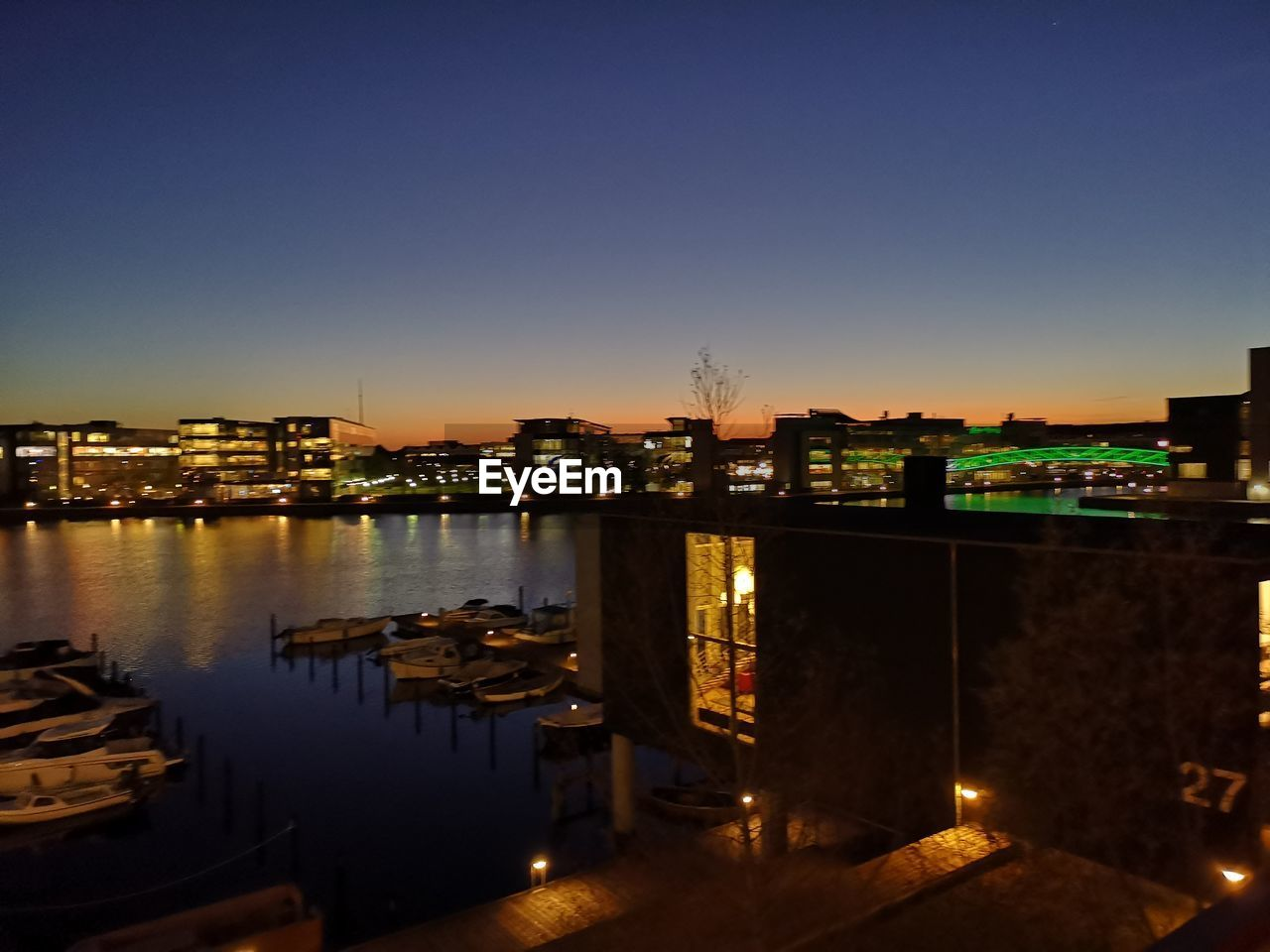 ILLUMINATED BUILDINGS BY RIVER AGAINST CLEAR SKY AT DUSK