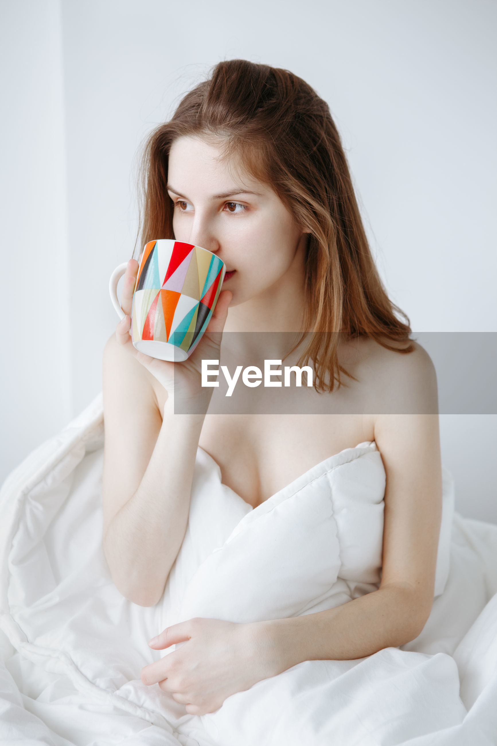 Young woman having drink while sitting on bed