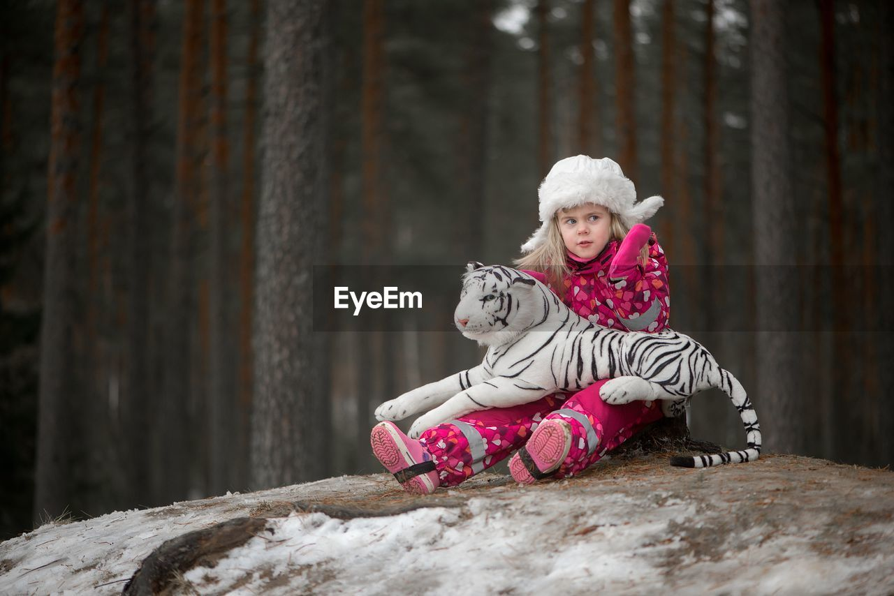 Girl in warm clothing gesturing while sitting with toy tiger by trees in forest