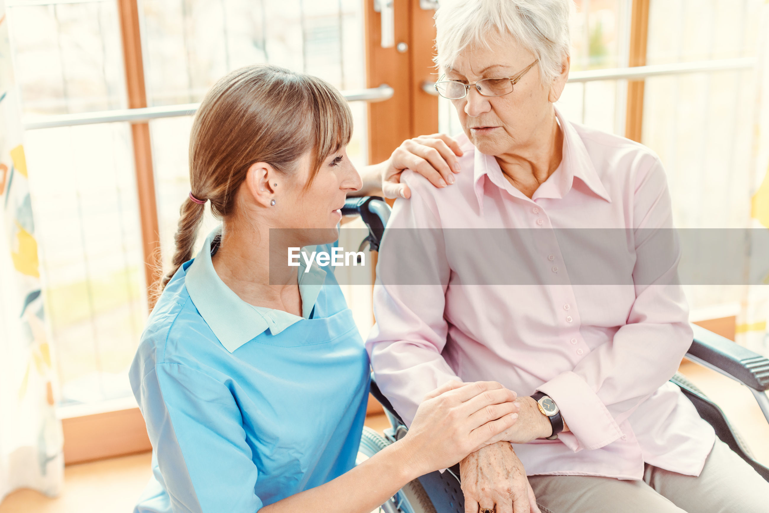 Caretaker consoling senior woman at nursing home
