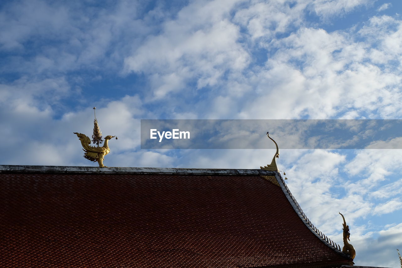 Low angle view of statue on roof of building against sky
