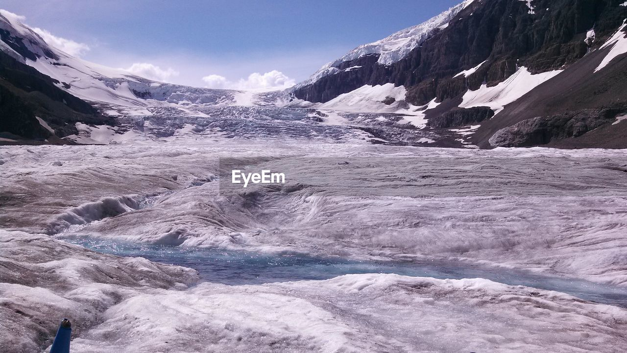 Scenic View Of River Stream By Frozen Landscape Against Sky