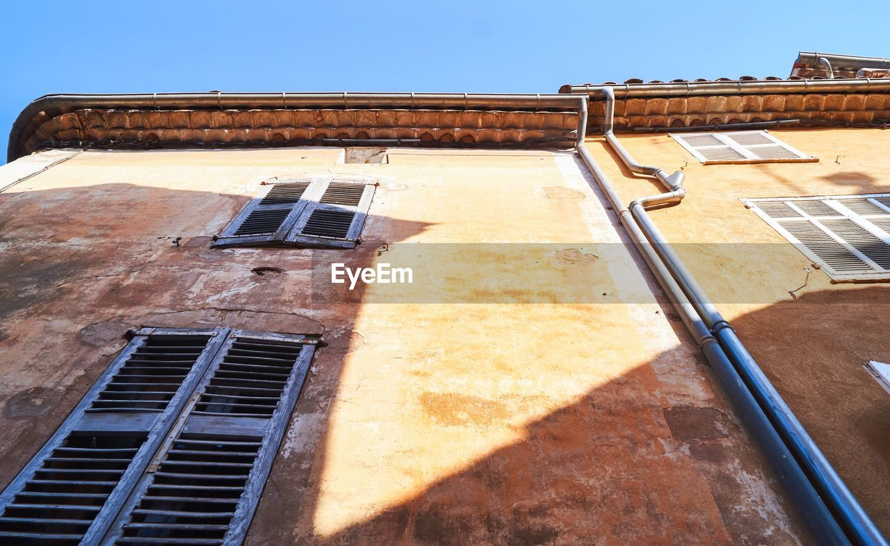 building exterior, architecture, built structure, window, sunlight, building, sky, no people, nature, day, shadow, low angle view, residential district, outdoors, house, blue, clear sky, old, sunny, wall - building feature