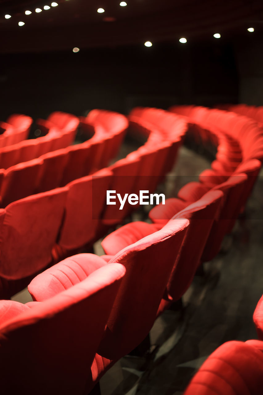 red, seat, chair, indoors, in a row, auditorium, movie theater, arts culture and entertainment, lighting equipment, leisure activity, large group of objects, repetition, stage theater, illuminated, focus on foreground, group of people, arrangement, film industry, empty