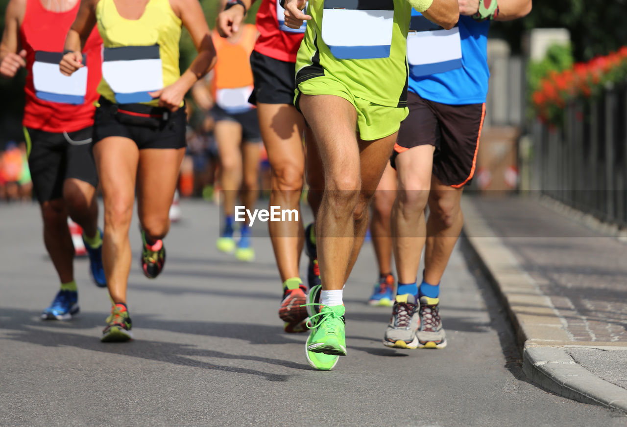 Low Section Of Male Athletes Running Marathon On Road