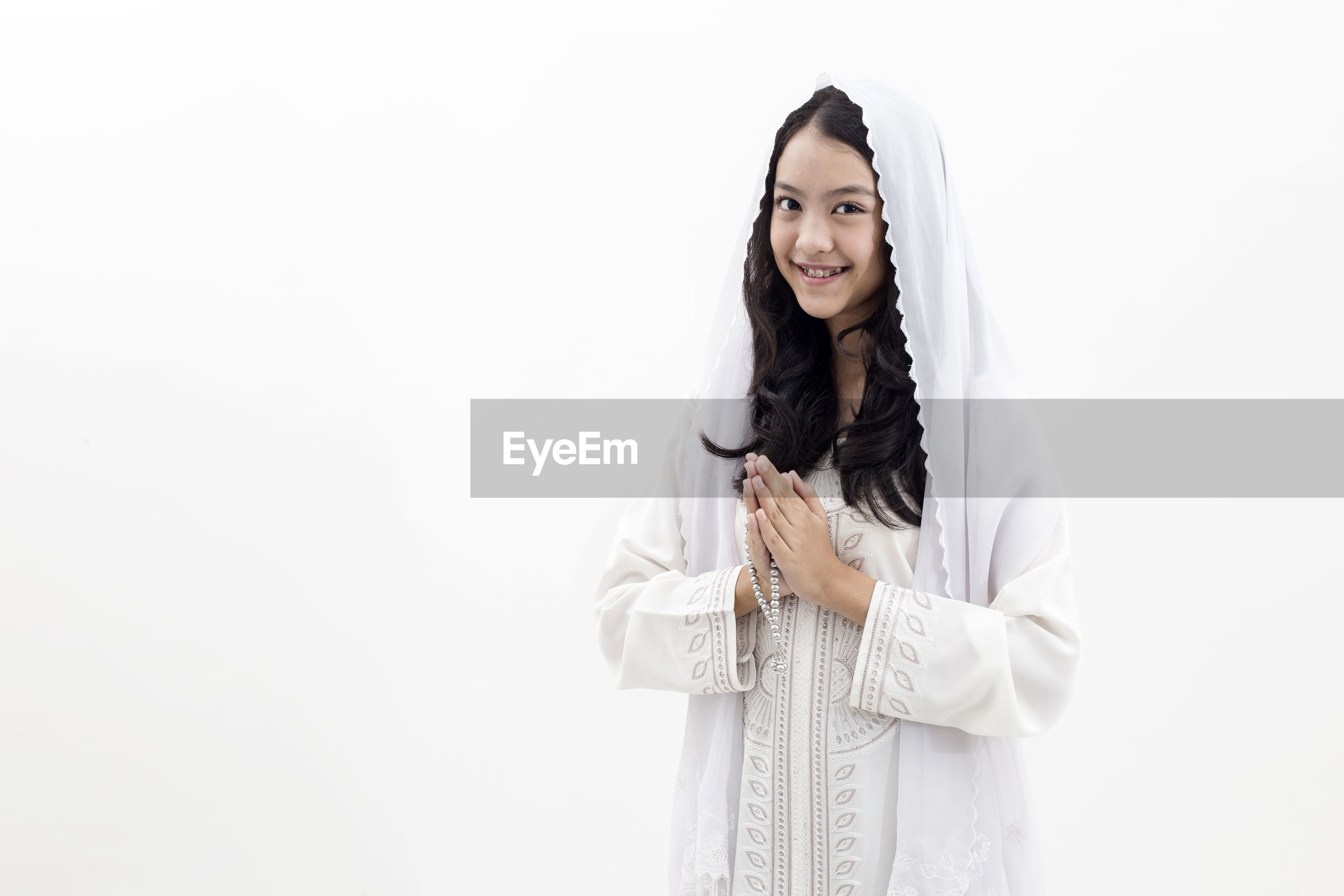 Portrait of smiling girl praying against white background