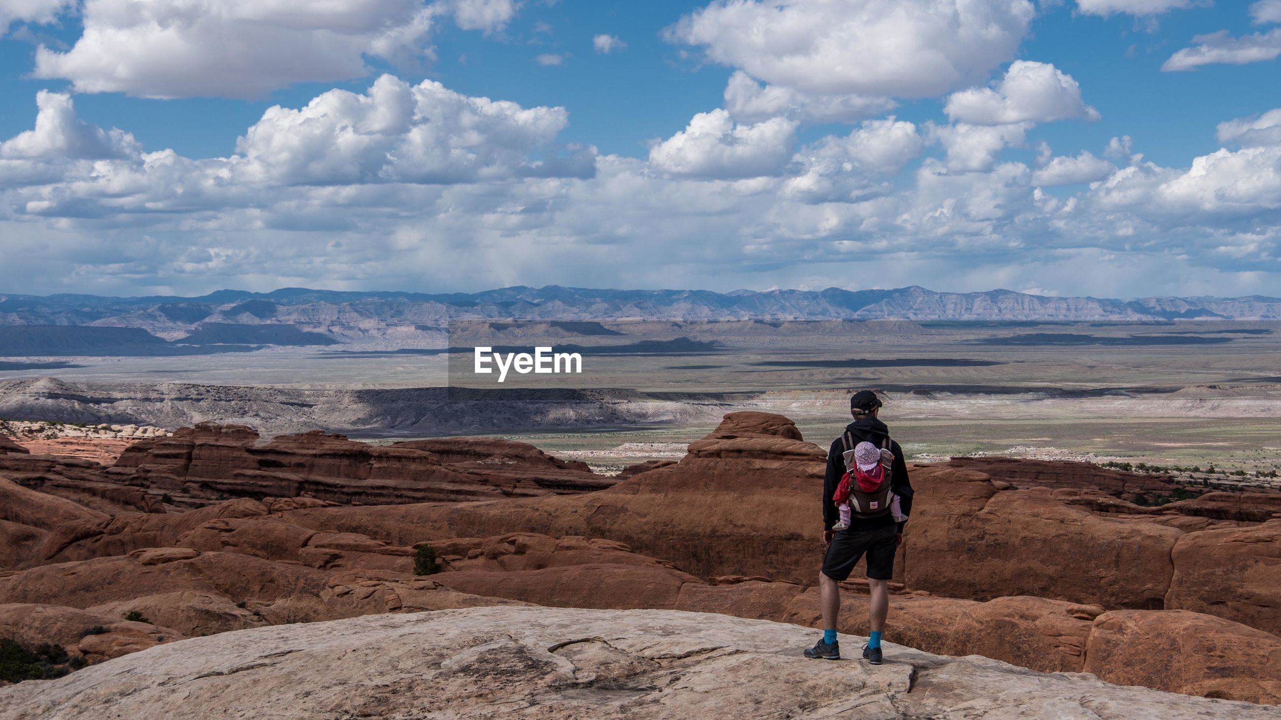 Rear view of man with baby carrier standing at arches national park