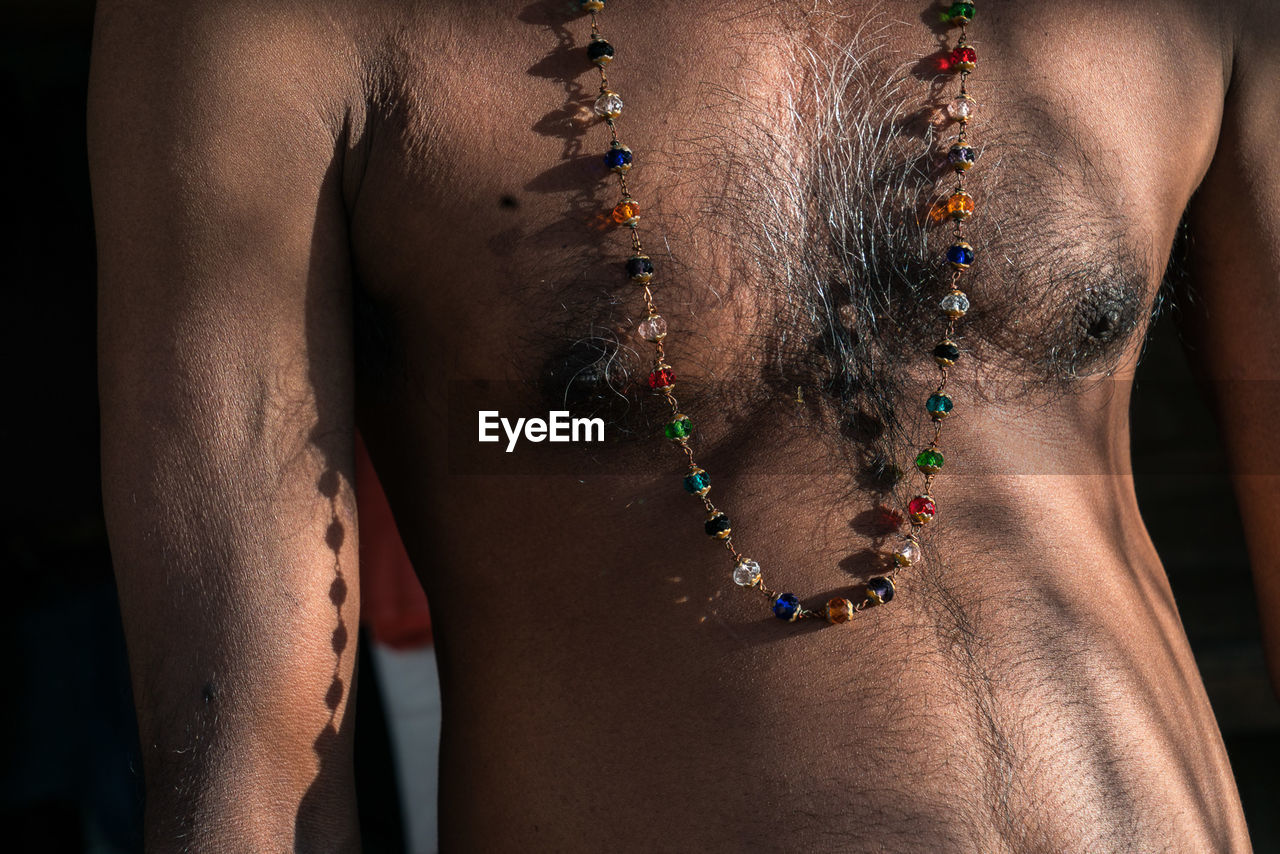 Midsection Of Shirtless Man Wearing Necklace