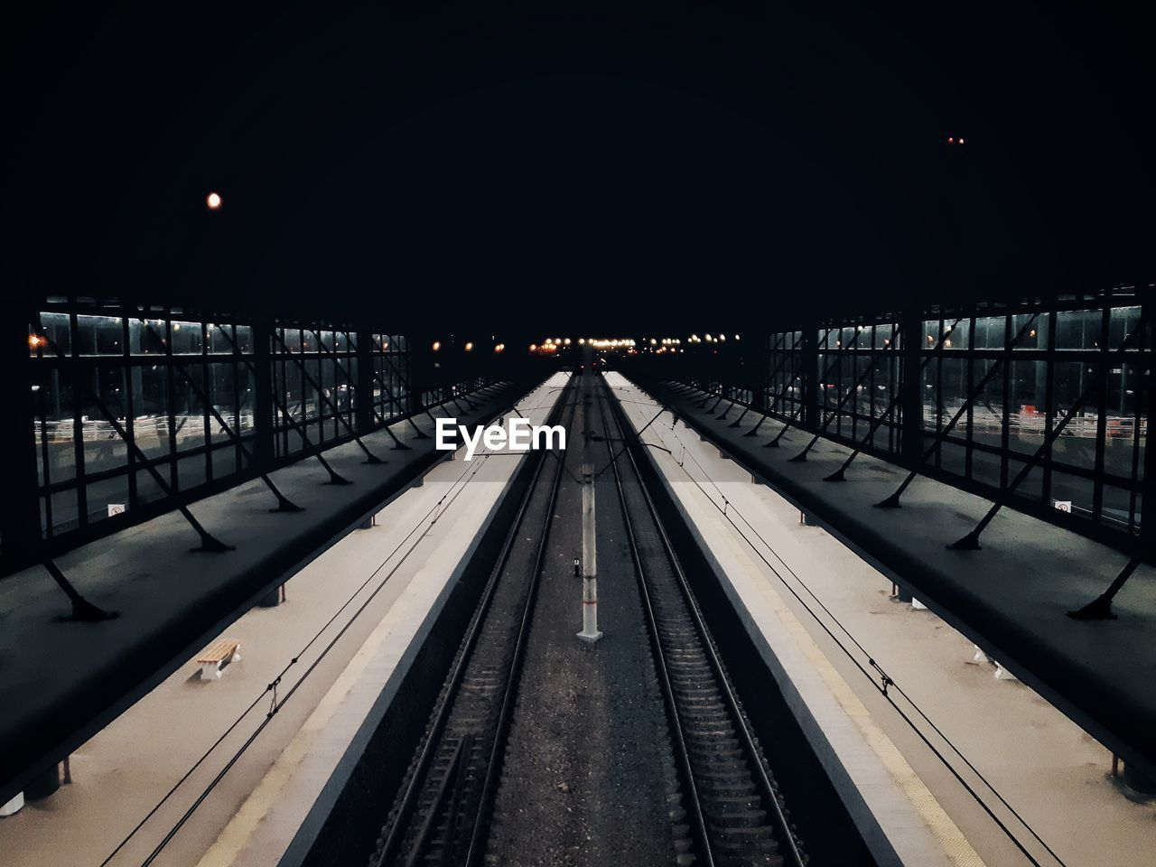 transportation, railroad track, rail transportation, track, architecture, the way forward, illuminated, direction, night, sky, built structure, diminishing perspective, nature, no people, connection, railing, outdoors, empty, railroad station, mode of transportation, platform, long