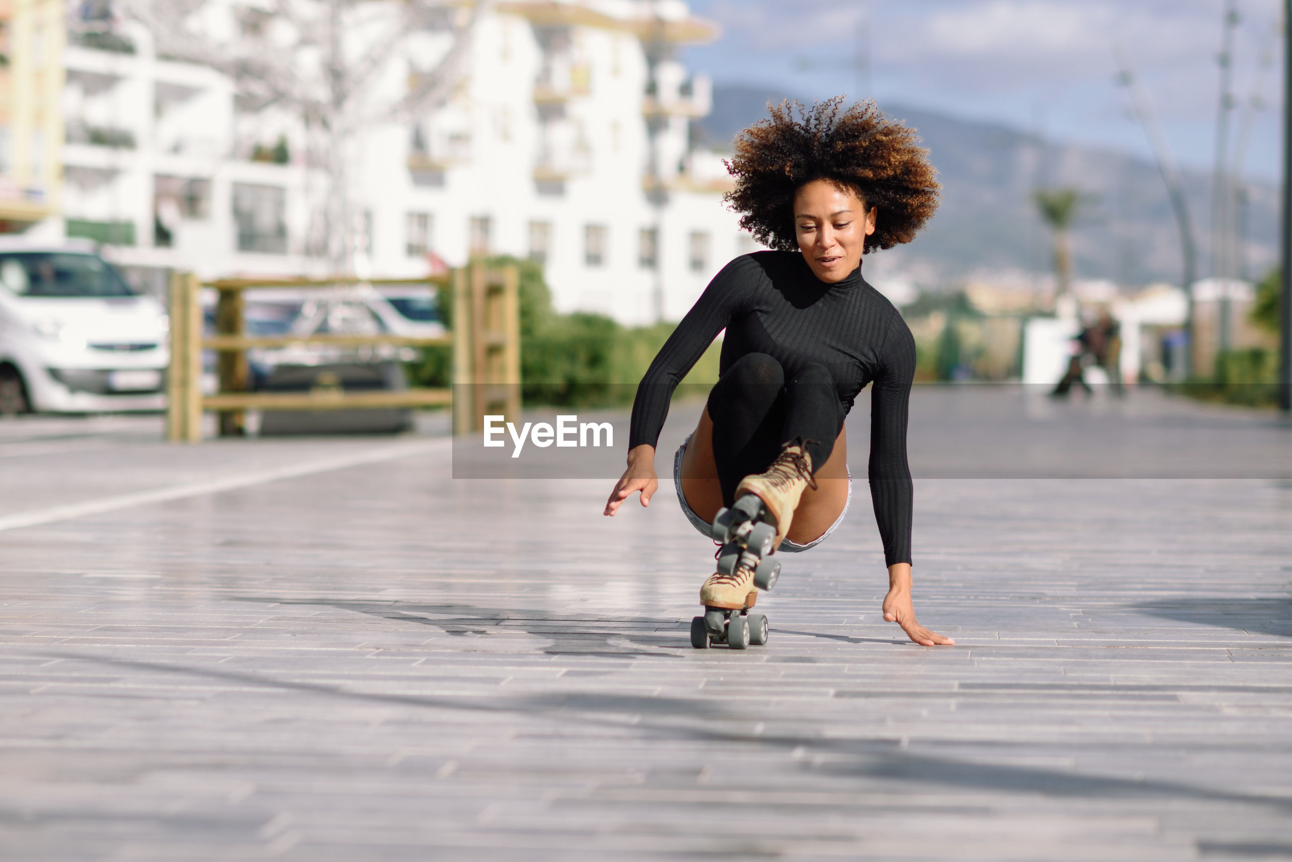 Young woman roller skating on sidewalk in city