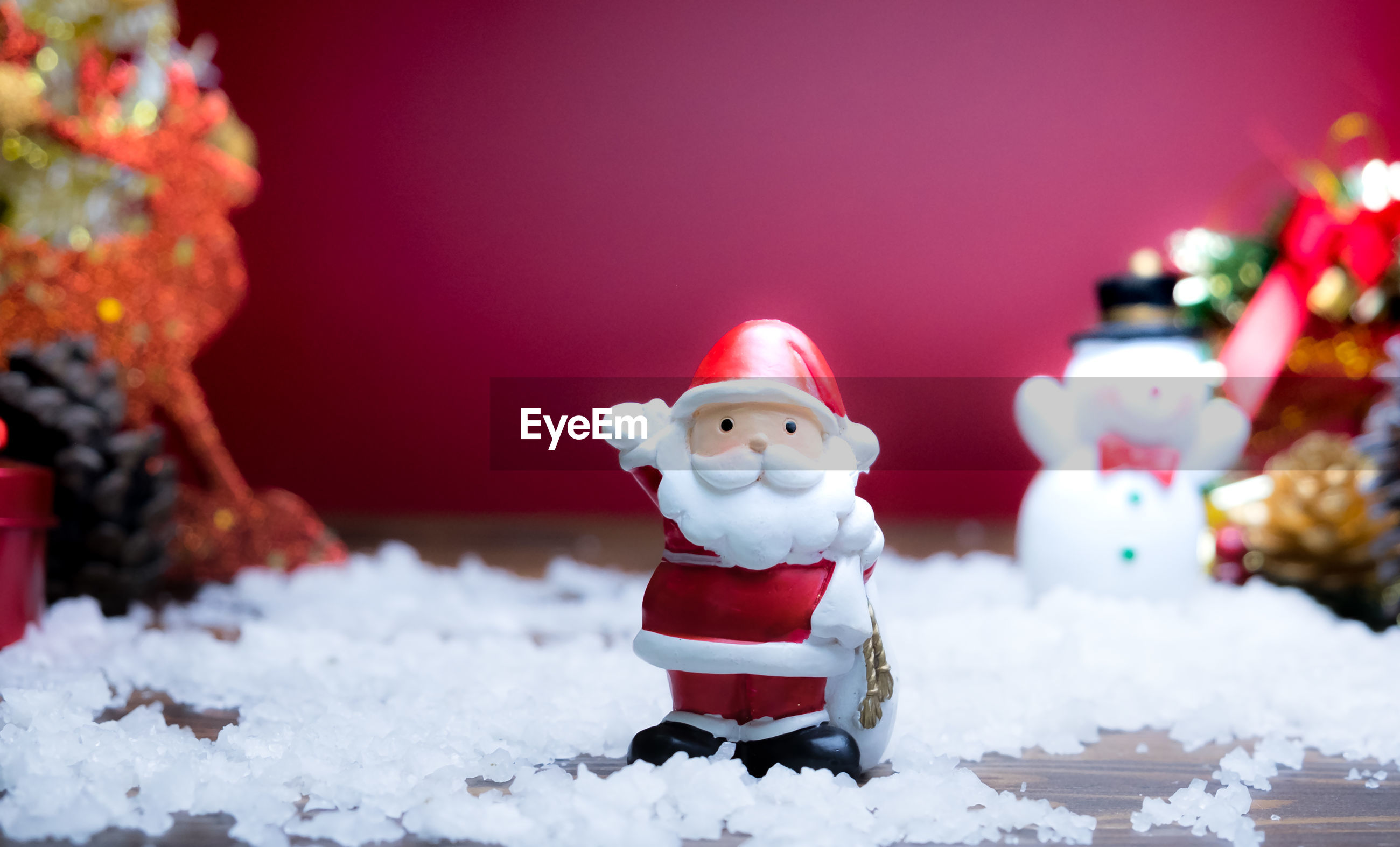 Close-up of santa by christmas present in snow