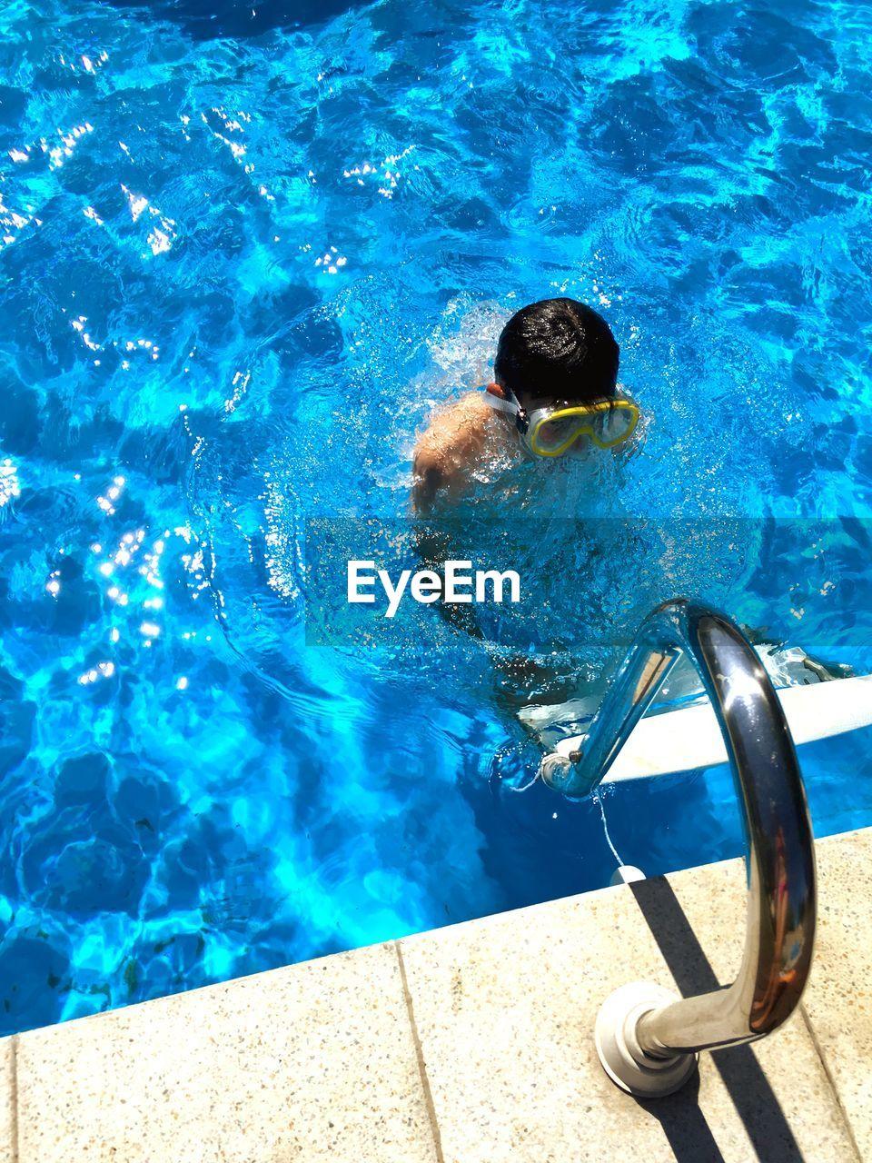 High angle view of teenage boy swimming in pool