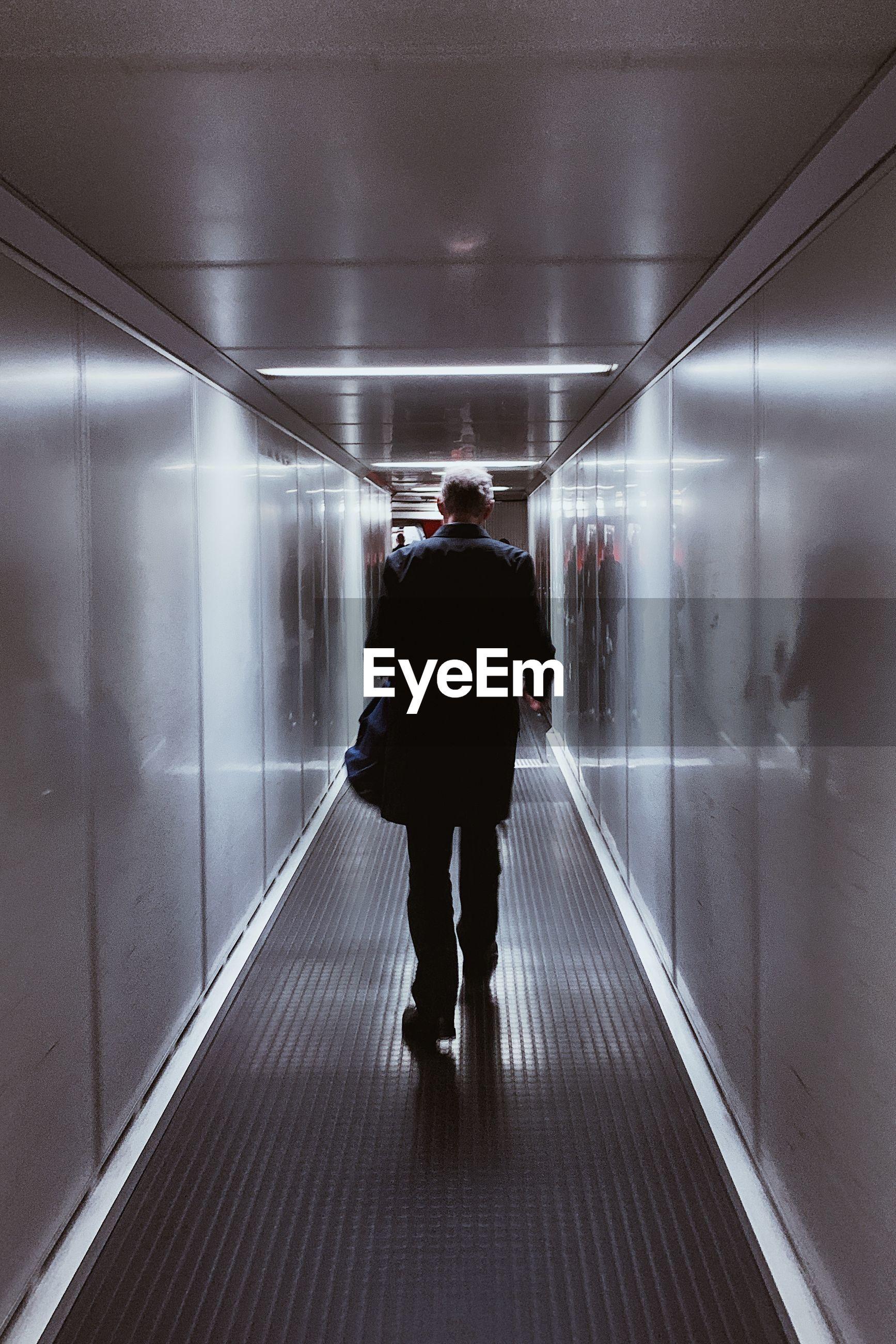 REAR VIEW OF MAN WALKING IN ILLUMINATED UNDERGROUND WALKWAY