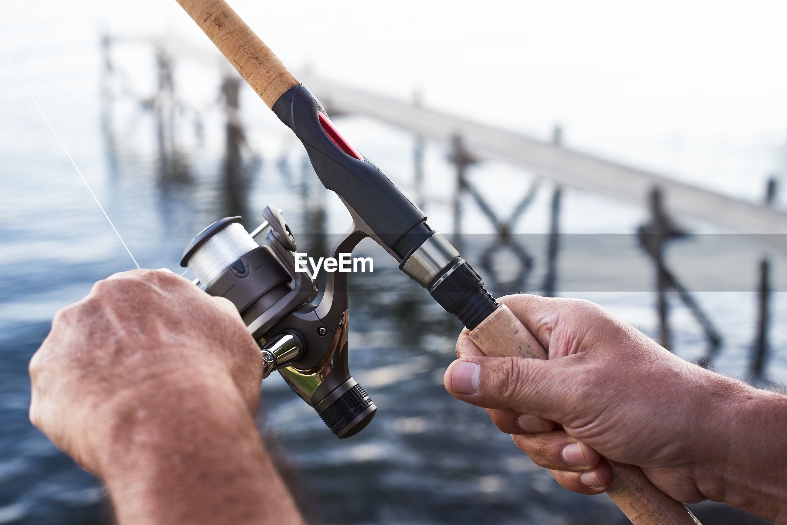 Cropped hands holding fishing rod