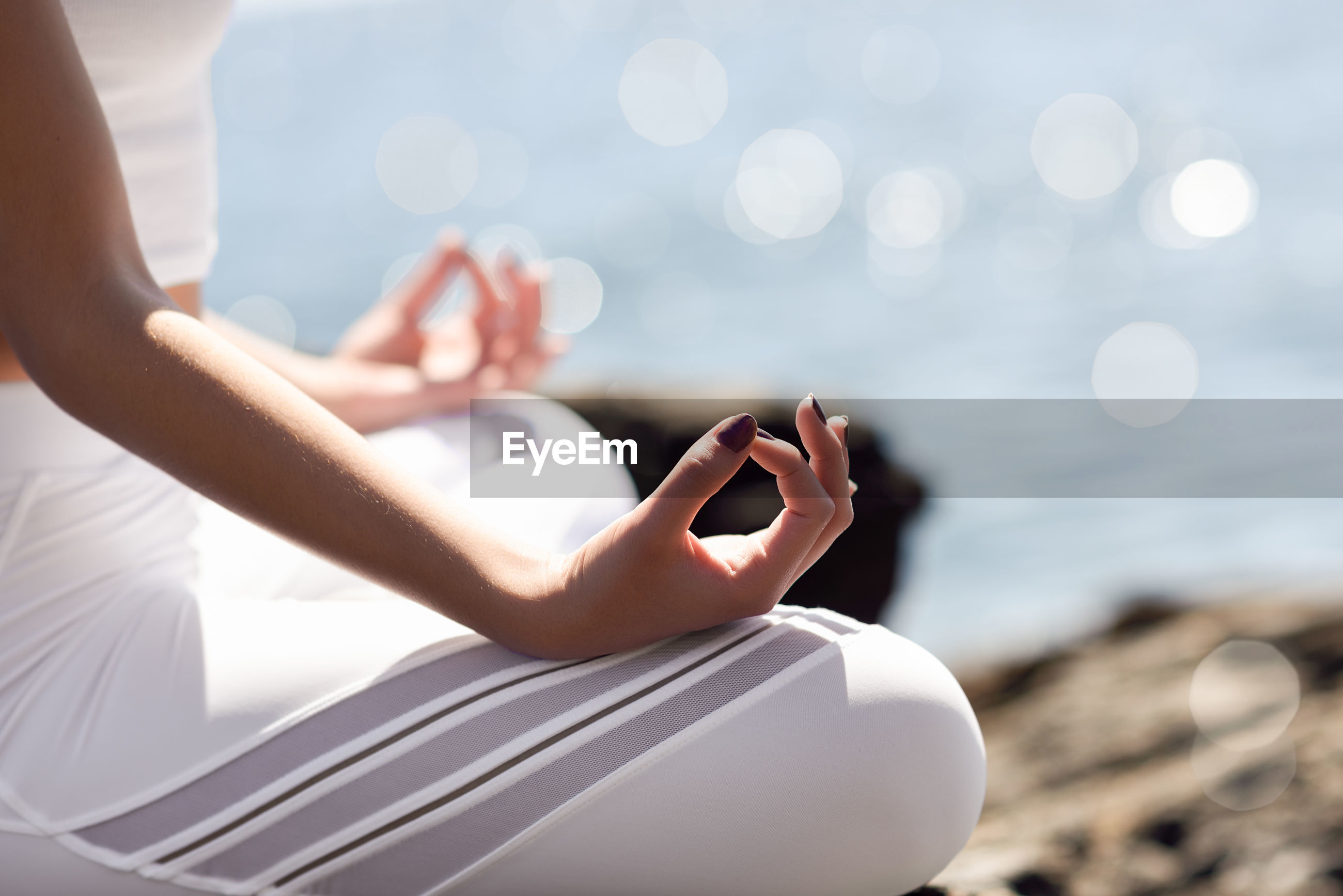 Midsection of woman meditating at beach