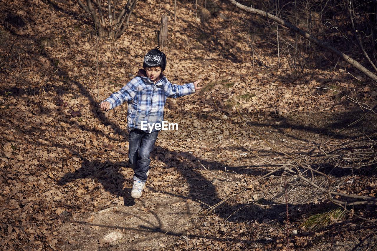 Full Length Of Boy Running In Forest