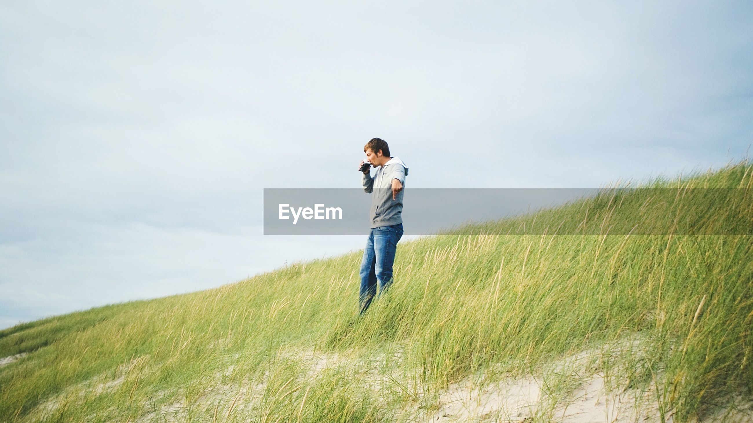 Side view of man drinking on grassy field against sky at wriedel