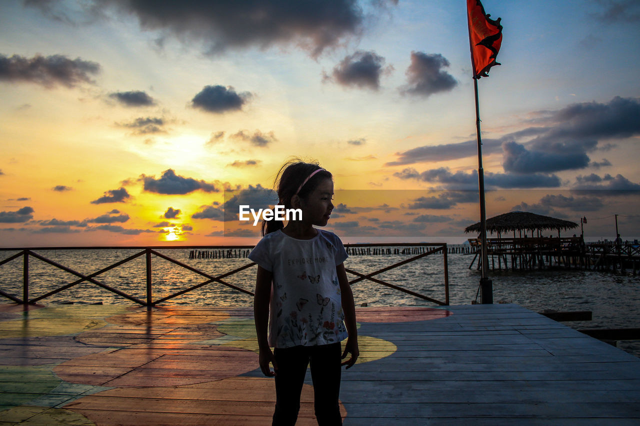 sky, sunset, water, cloud - sky, one person, standing, real people, sea, beauty in nature, scenics - nature, lifestyles, leisure activity, flag, nature, women, orange color, pier, three quarter length, outdoors, horizon over water