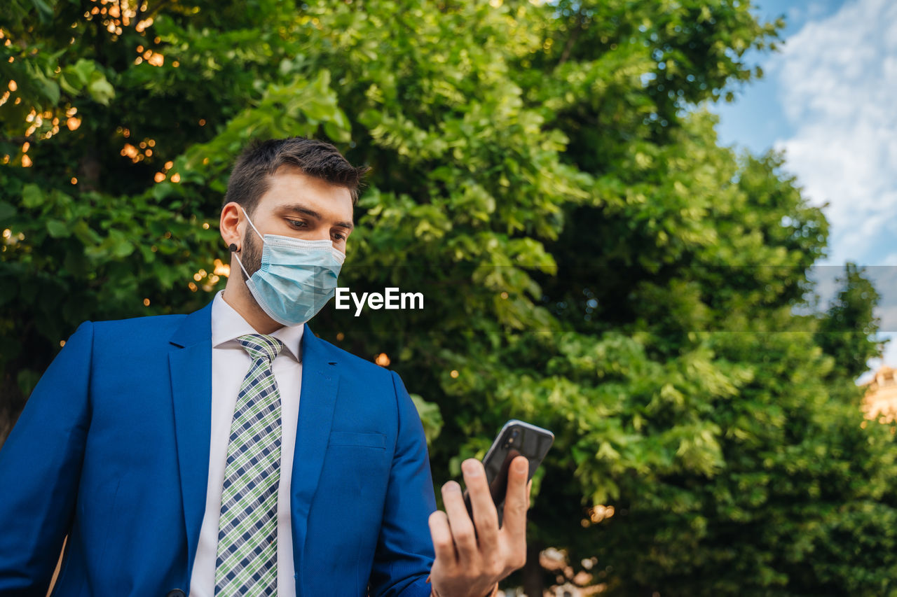 Young elegant businessman with a surgical mask looks at the phone in the park