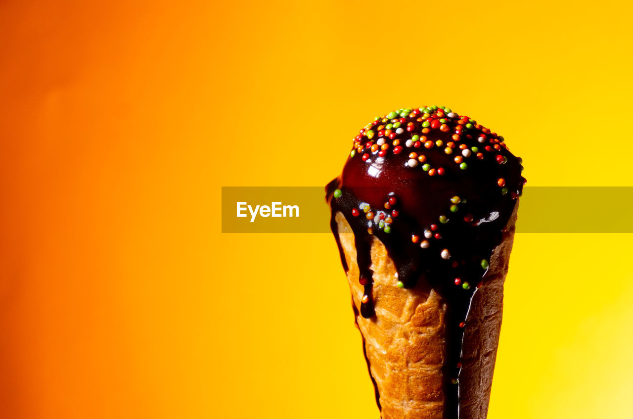 sweet food, food and drink, sweet, food, indulgence, dessert, unhealthy eating, studio shot, colored background, close-up, freshness, temptation, sprinkles, frozen food, ice cream, still life, frozen, yellow background, indoors, ready-to-eat, no people, orange background